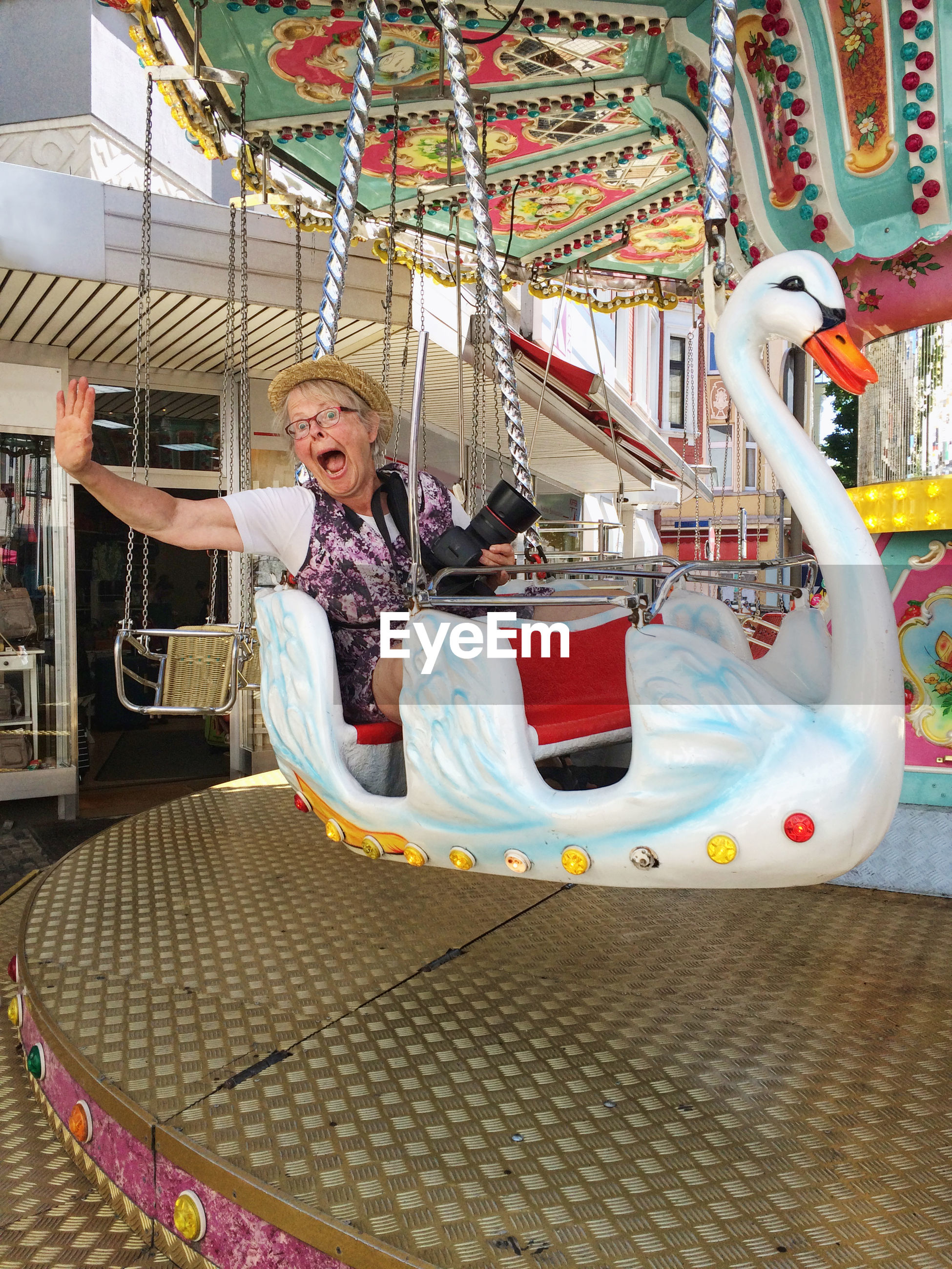 amusement park, amusement park ride, leisure activity, carousel, enjoyment, arts culture and entertainment, childhood, fun, carousel horses, lifestyles, smiling, happiness, looking at camera, full length, elementary age, girls, merry-go-round, real people, playing, day, outdoors, one person, people