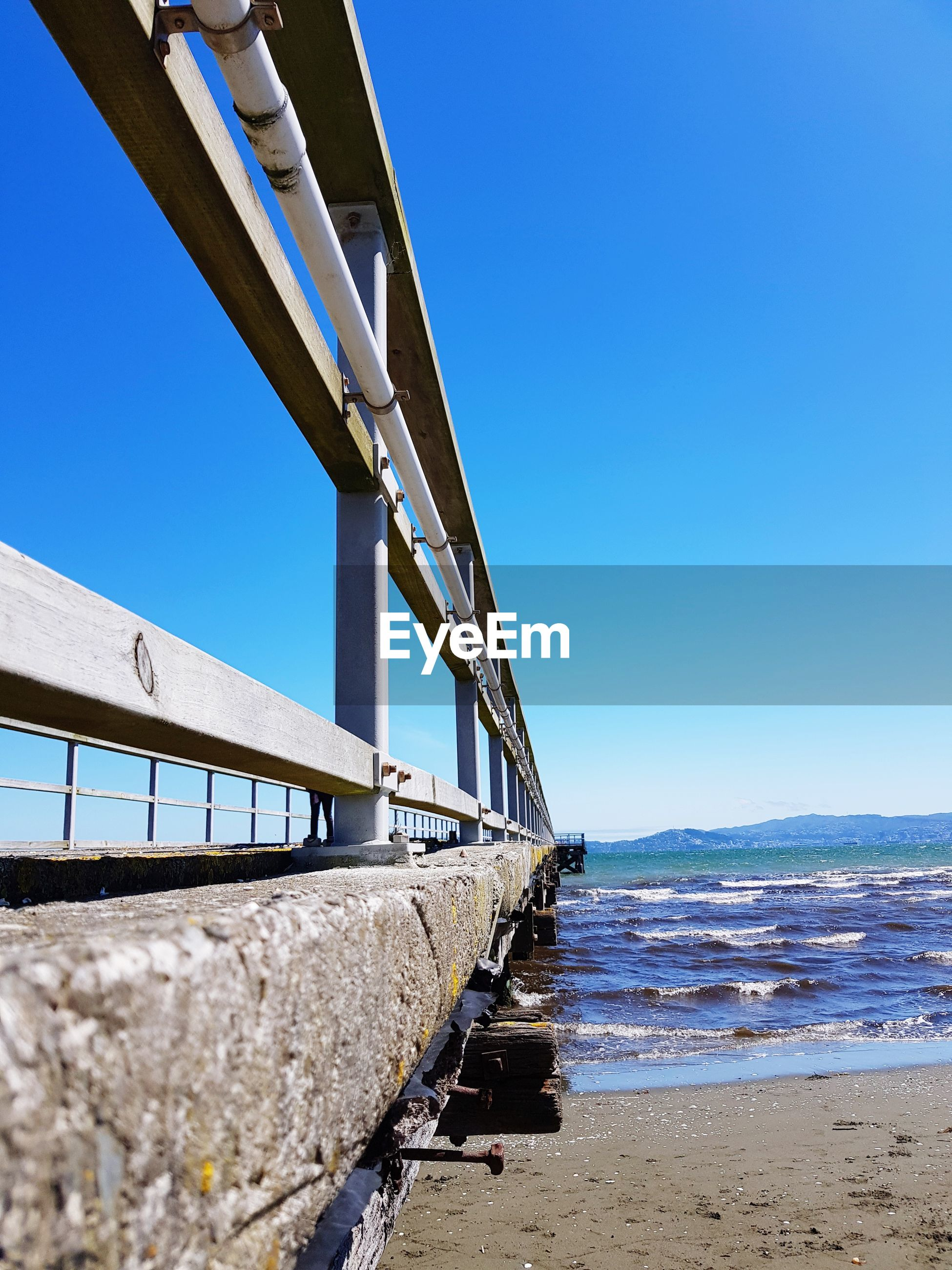 LOW ANGLE VIEW OF BRIDGE ON BEACH AGAINST CLEAR SKY