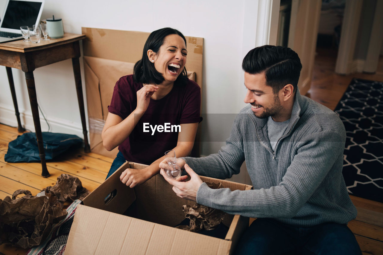 Laughing couple unpacking cardboard box while sitting on floor at home