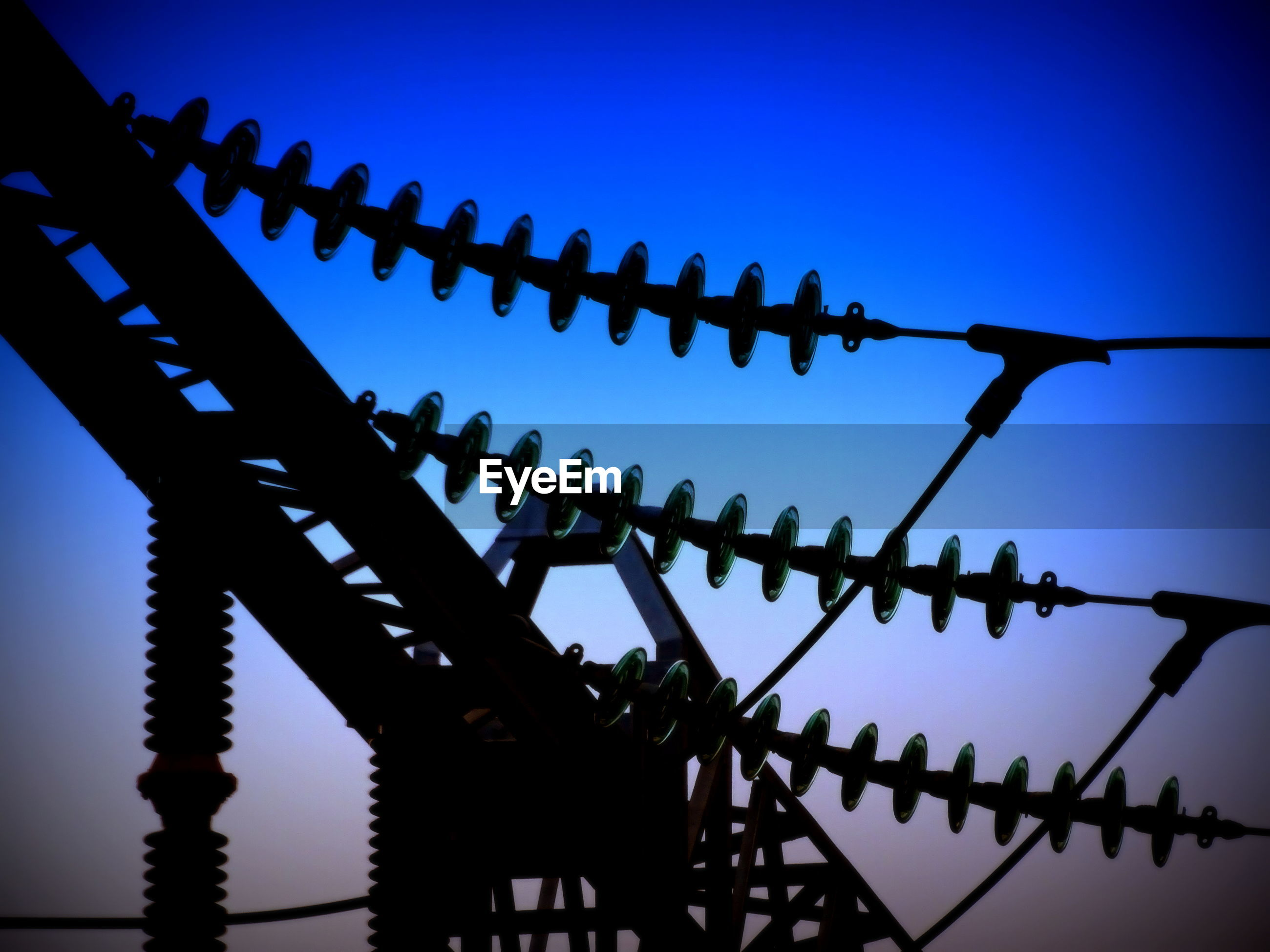 Close-up of electricity pylons against clear blue sky