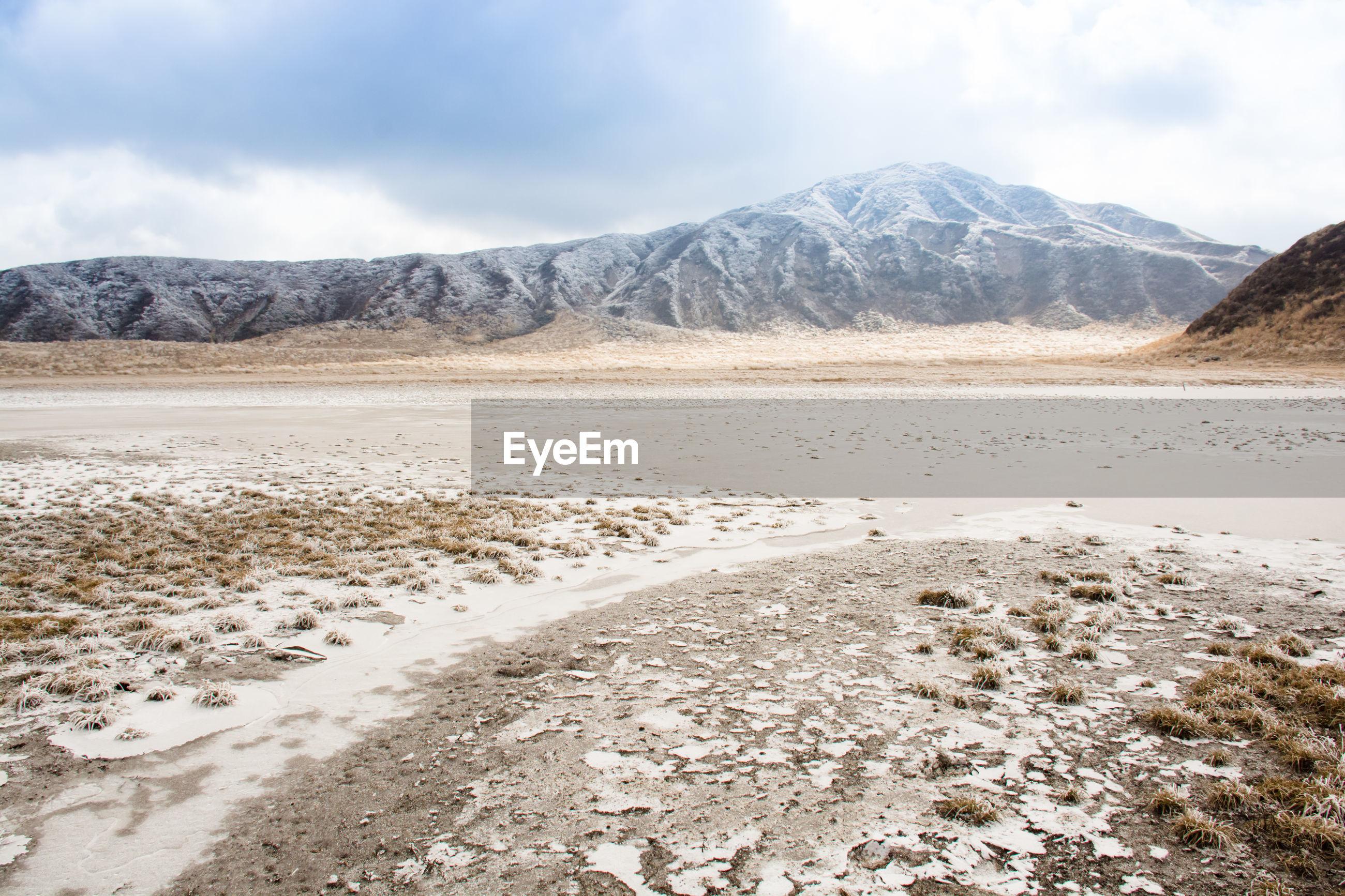 SURFACE LEVEL OF DESERT AGAINST MOUNTAIN RANGE