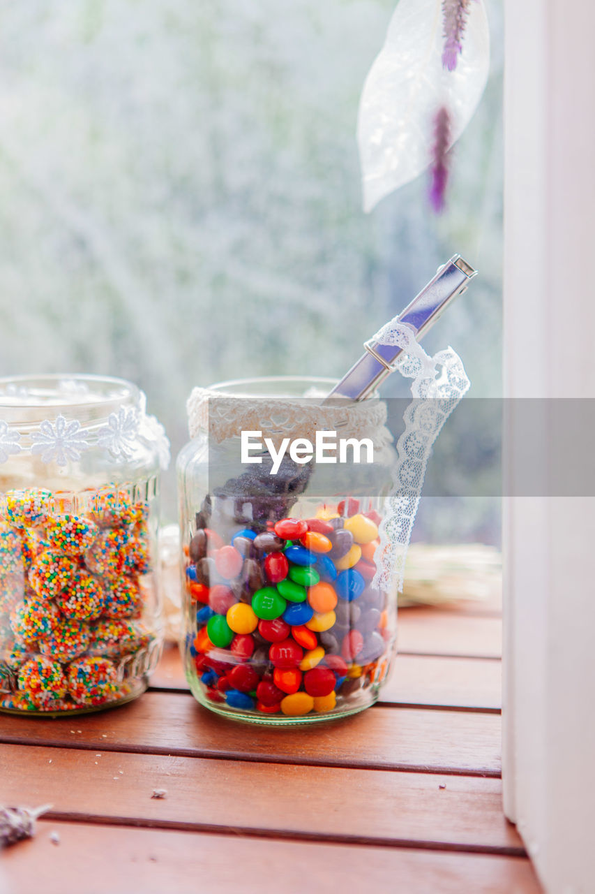 food and drink, sweet food, table, jar, food, container, sweet, indoors, still life, focus on foreground, glass - material, indulgence, freshness, multi colored, day, candy, temptation, unhealthy eating, transparent, no people, glass, snack
