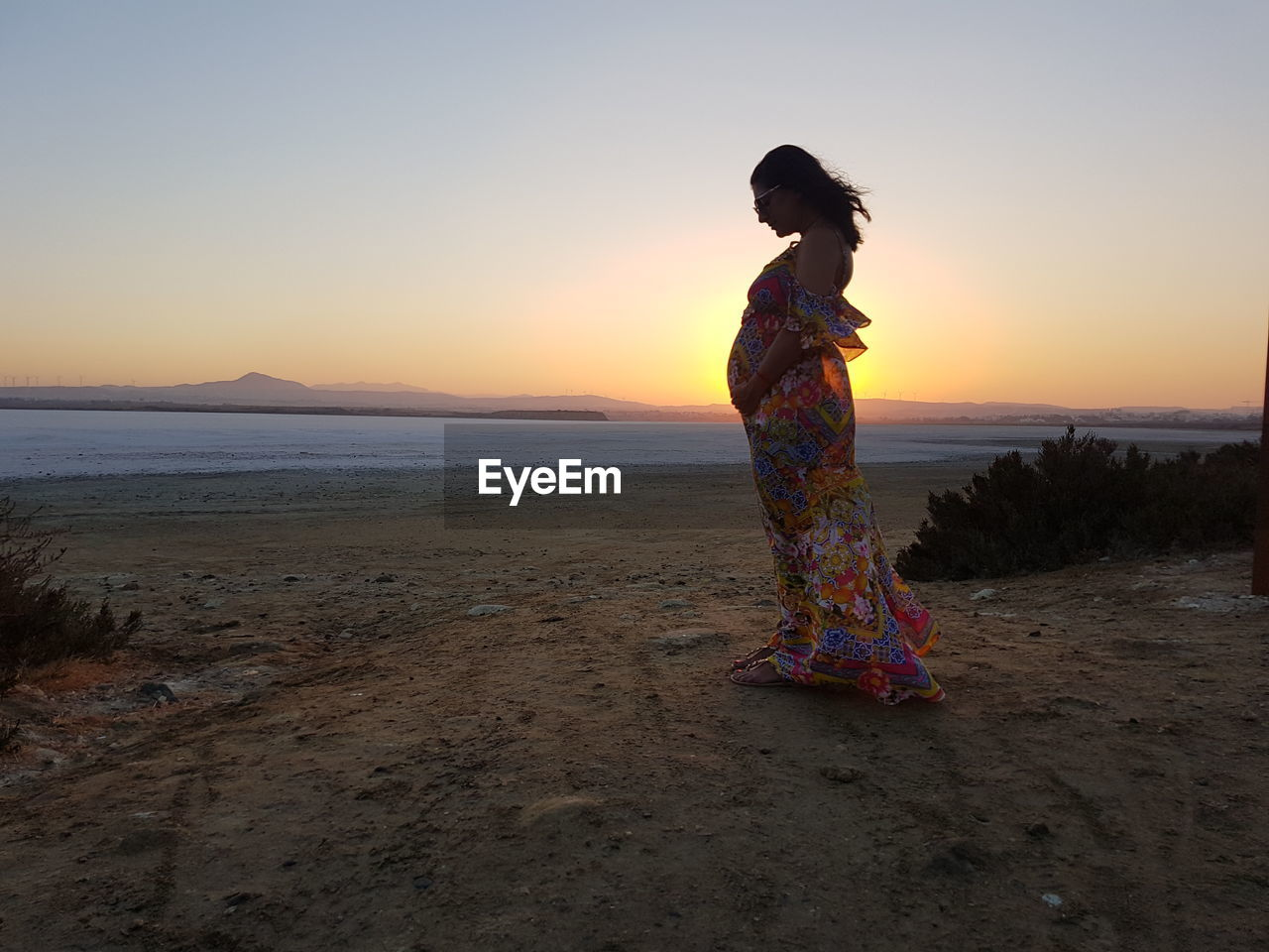 Side view of pregnant woman standing on sand at beach against sky during sunset