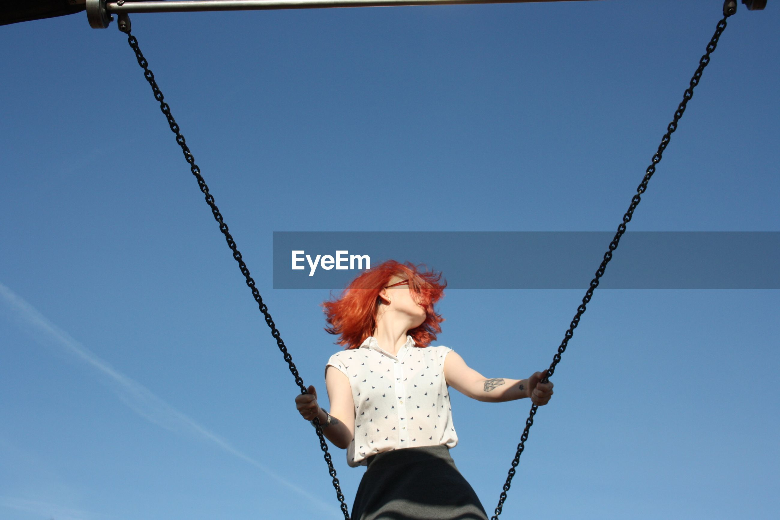 Young woman on swing against sky