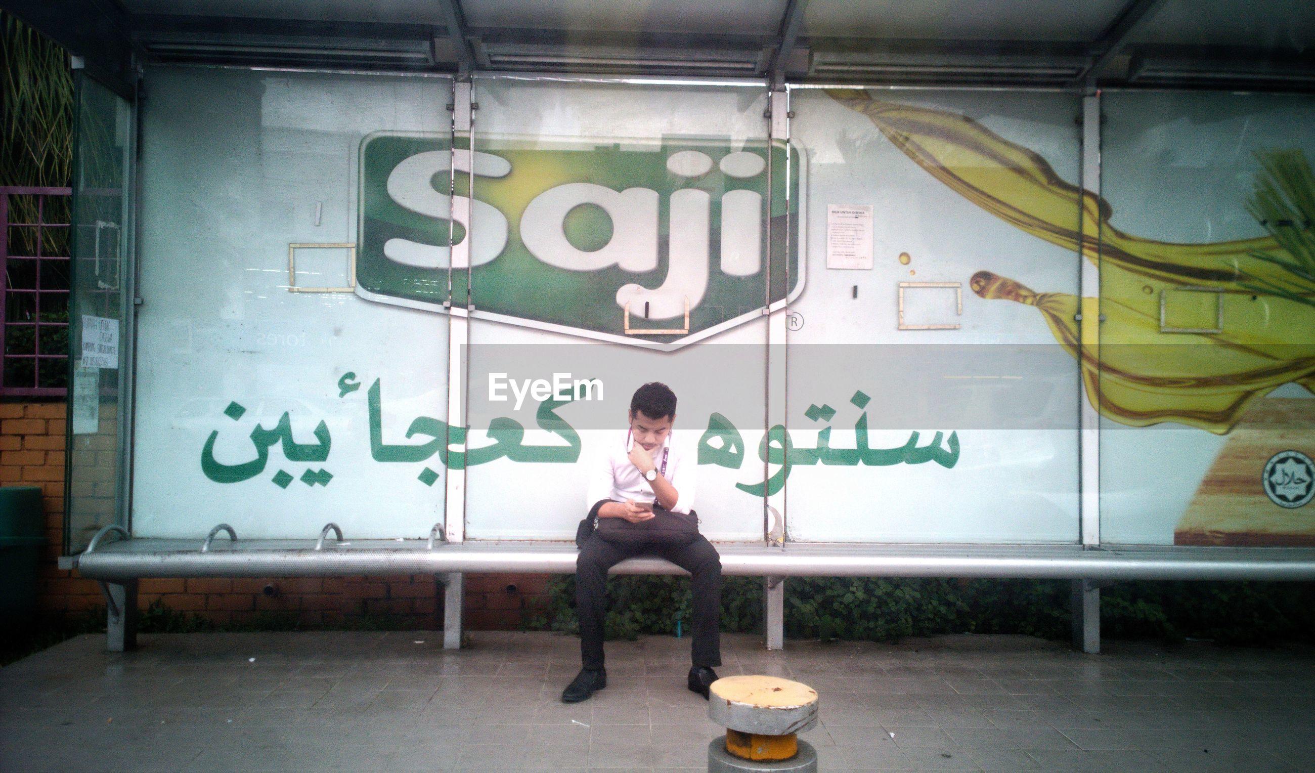 Full length of man sitting on bus stop