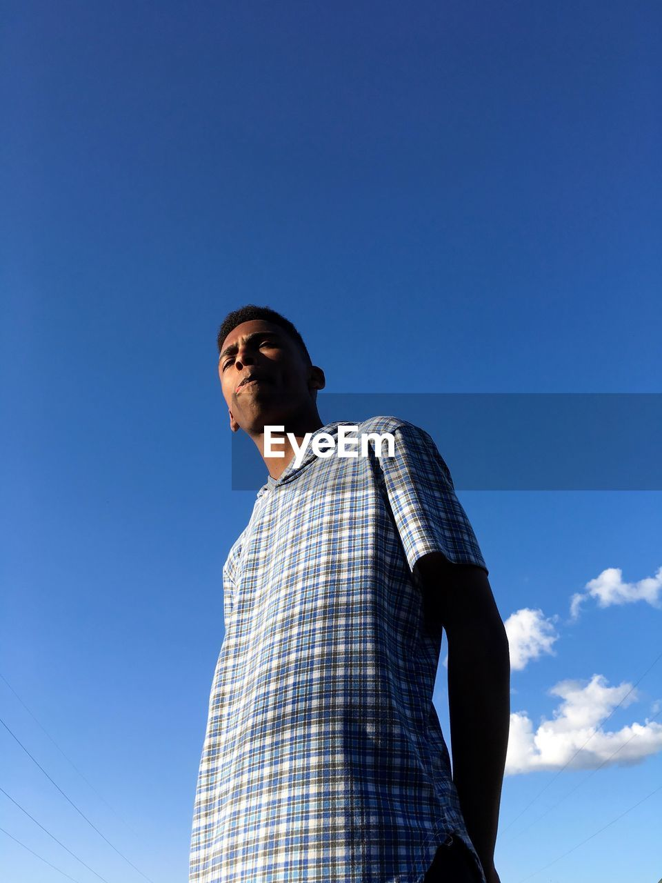Low angle view of man looking away against blue sky