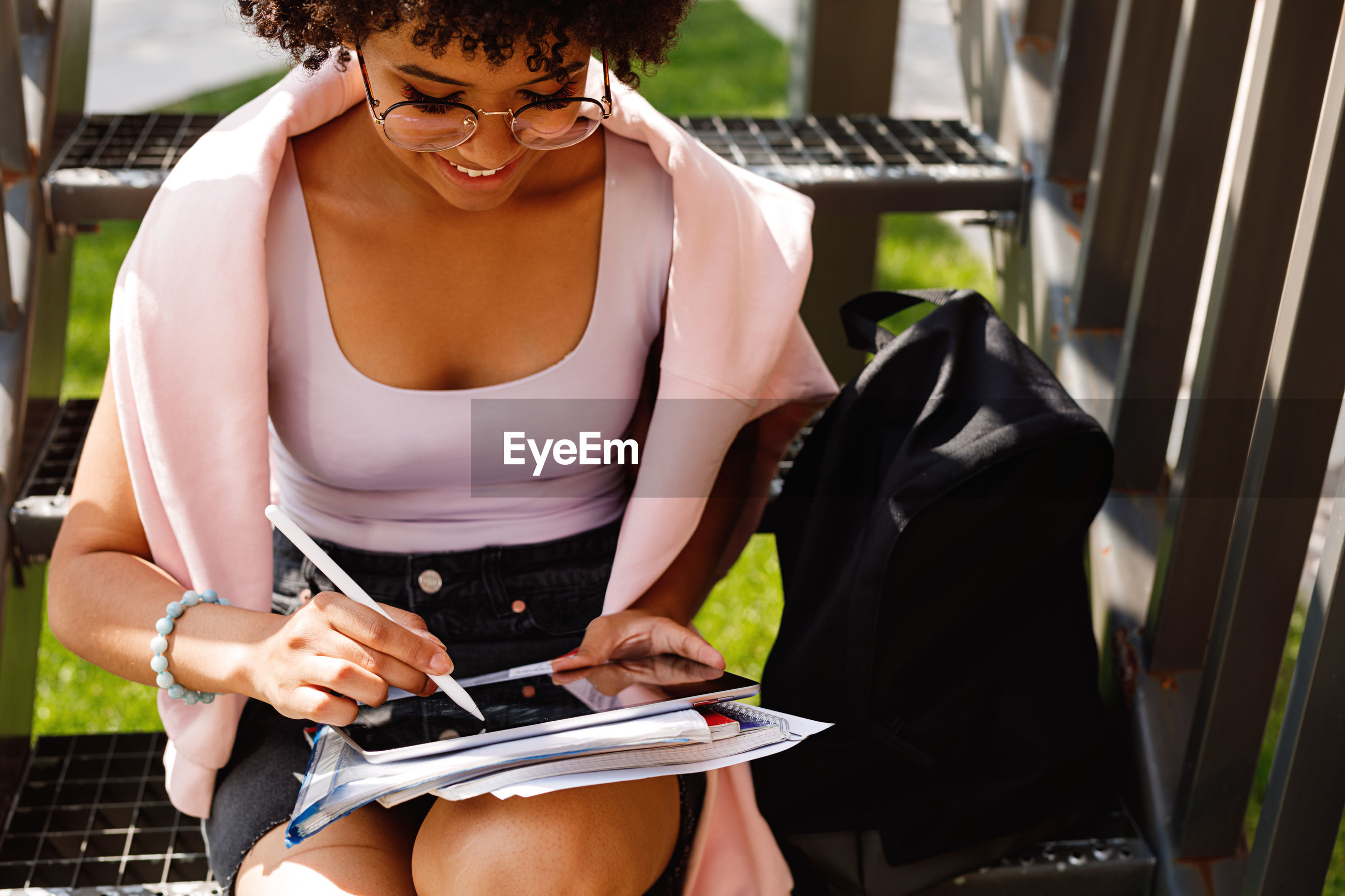 Young woman using digital tablet while sitting on steps