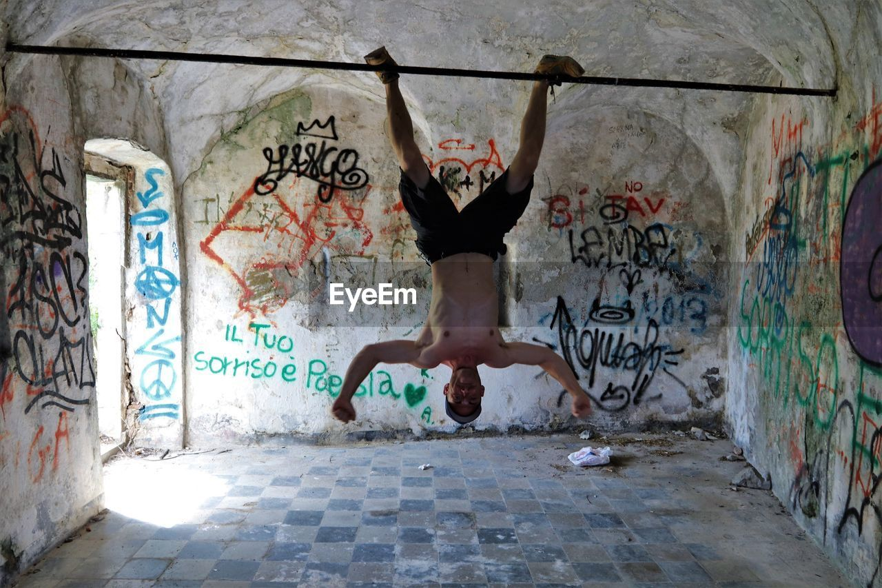 graffiti, full length, one person, architecture, wall - building feature, text, real people, art and craft, day, lifestyles, western script, creativity, jumping, built structure, mid-air, motion, outdoors, wall, young adult, human arm, arms raised