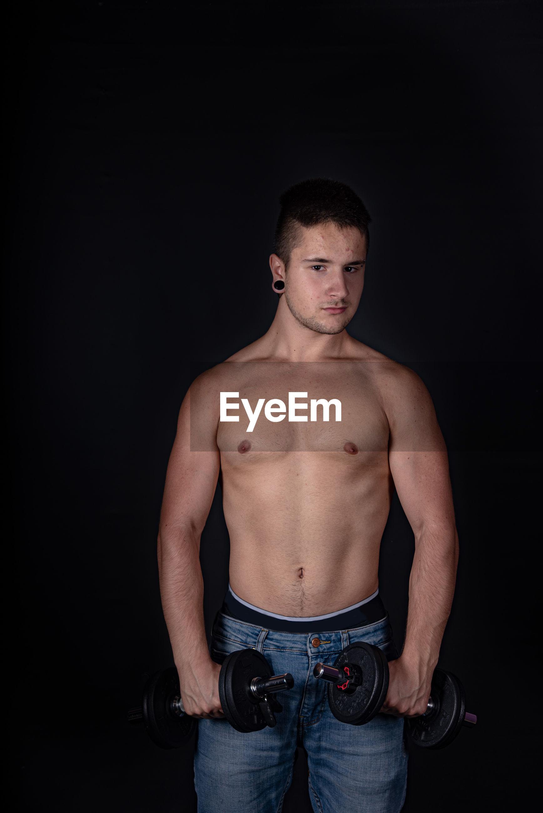 Portrait of shirtless man lifting dumbbells against black background