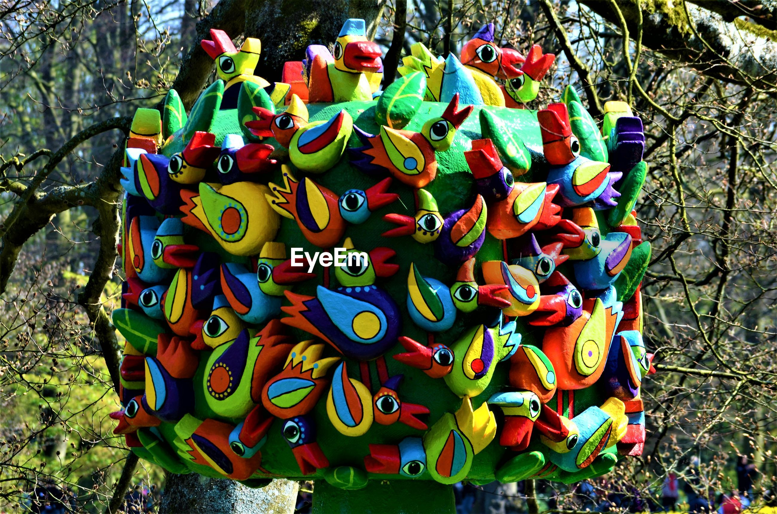 HIGH ANGLE VIEW OF MULTI COLORED TOY HANGING ON FIELD