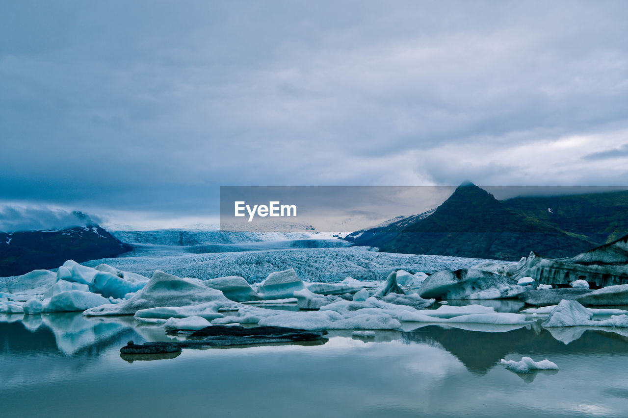 Glaciers in lake against sky