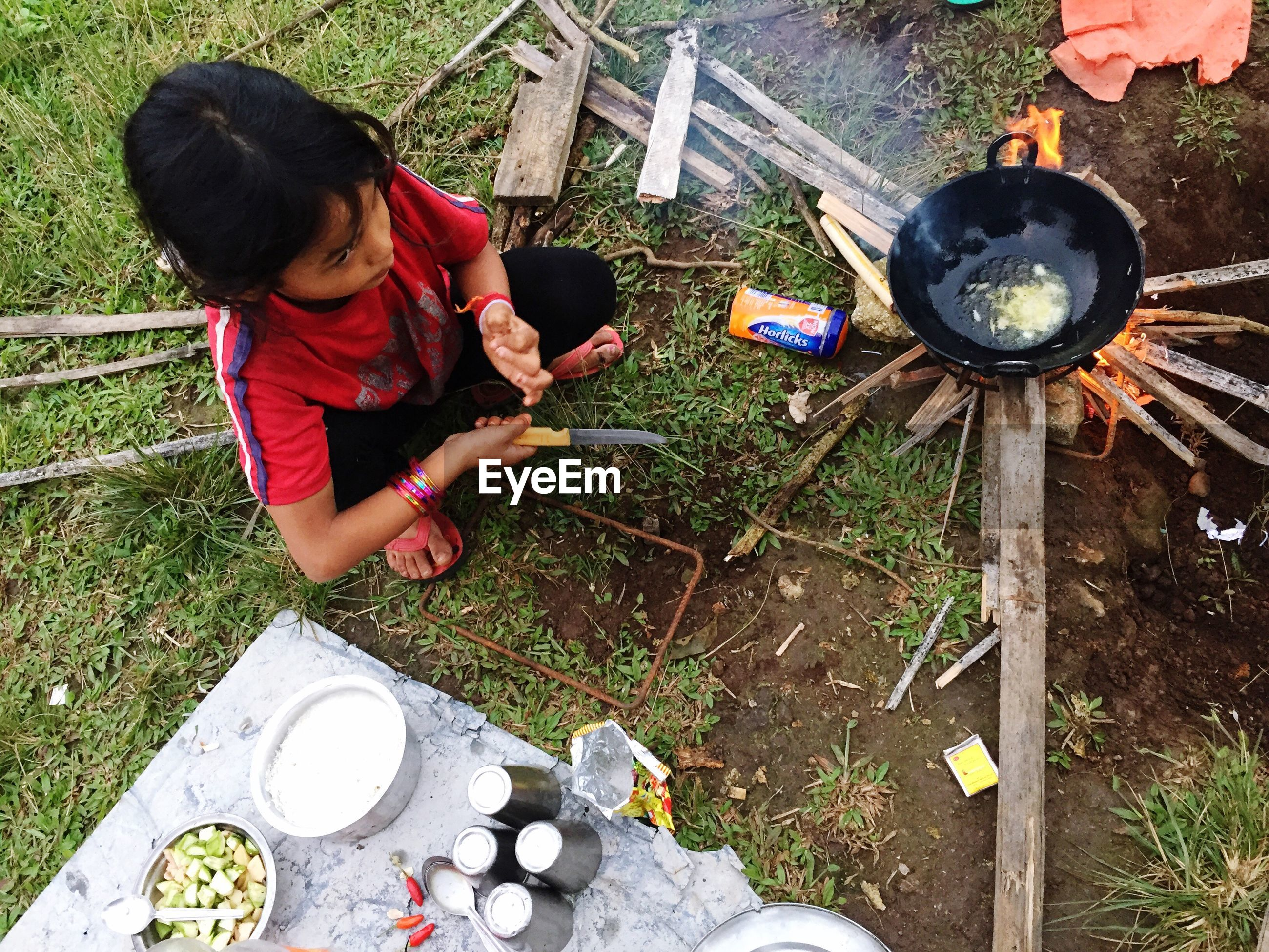 High angle view of girl preparing food in yard