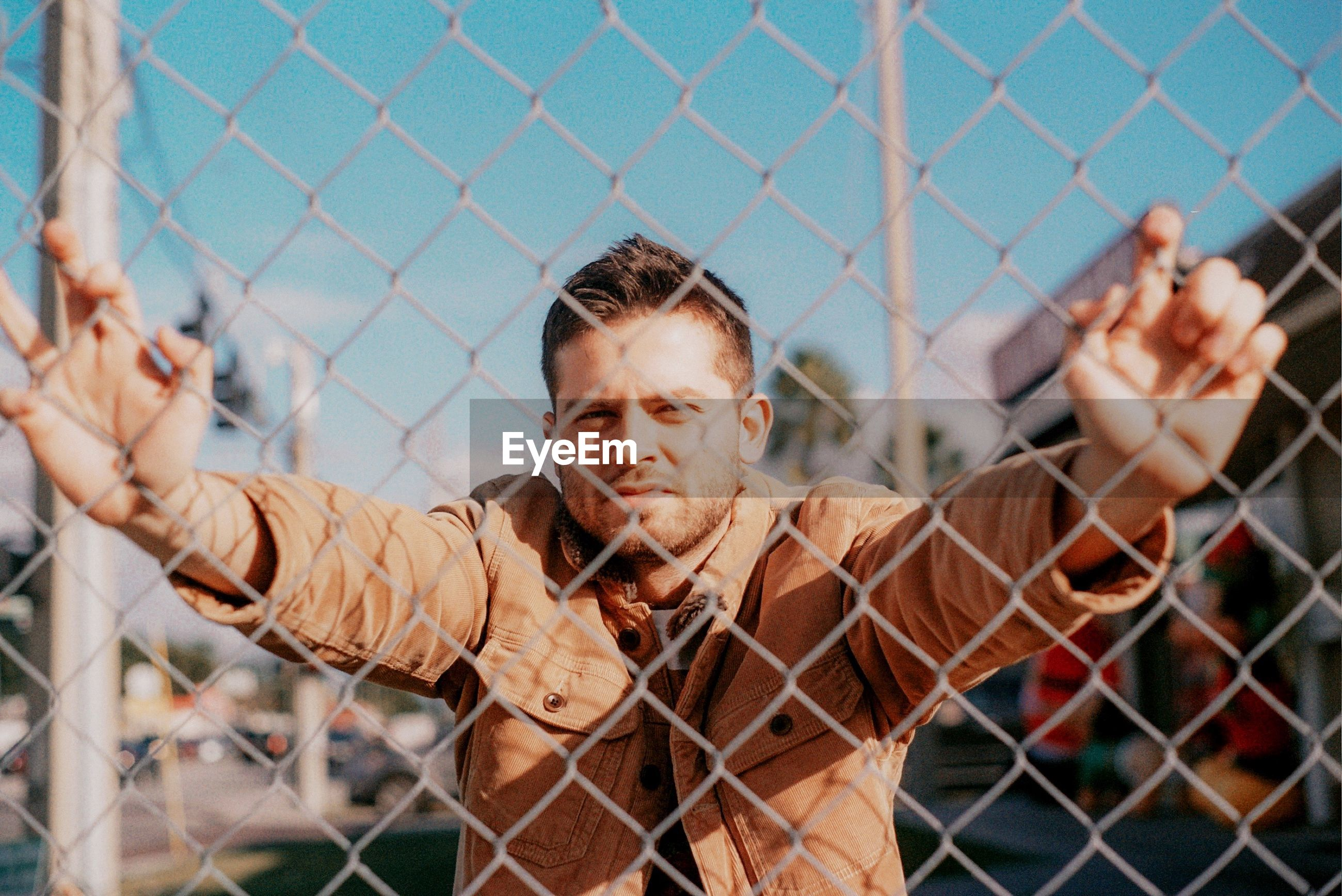 Portrait of man with arms raised against fence