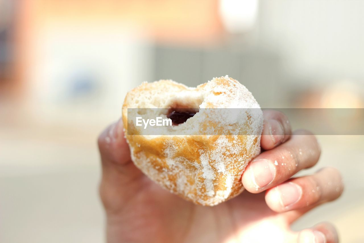 Cropped Image Of Hand Holding Donut
