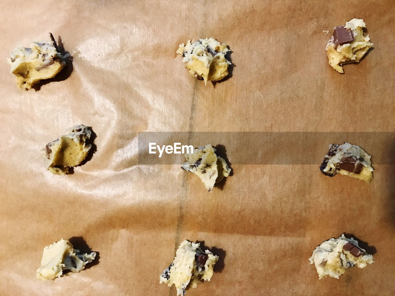 High Angle View Of Chocolate Chip Cookies Arranged On Paper