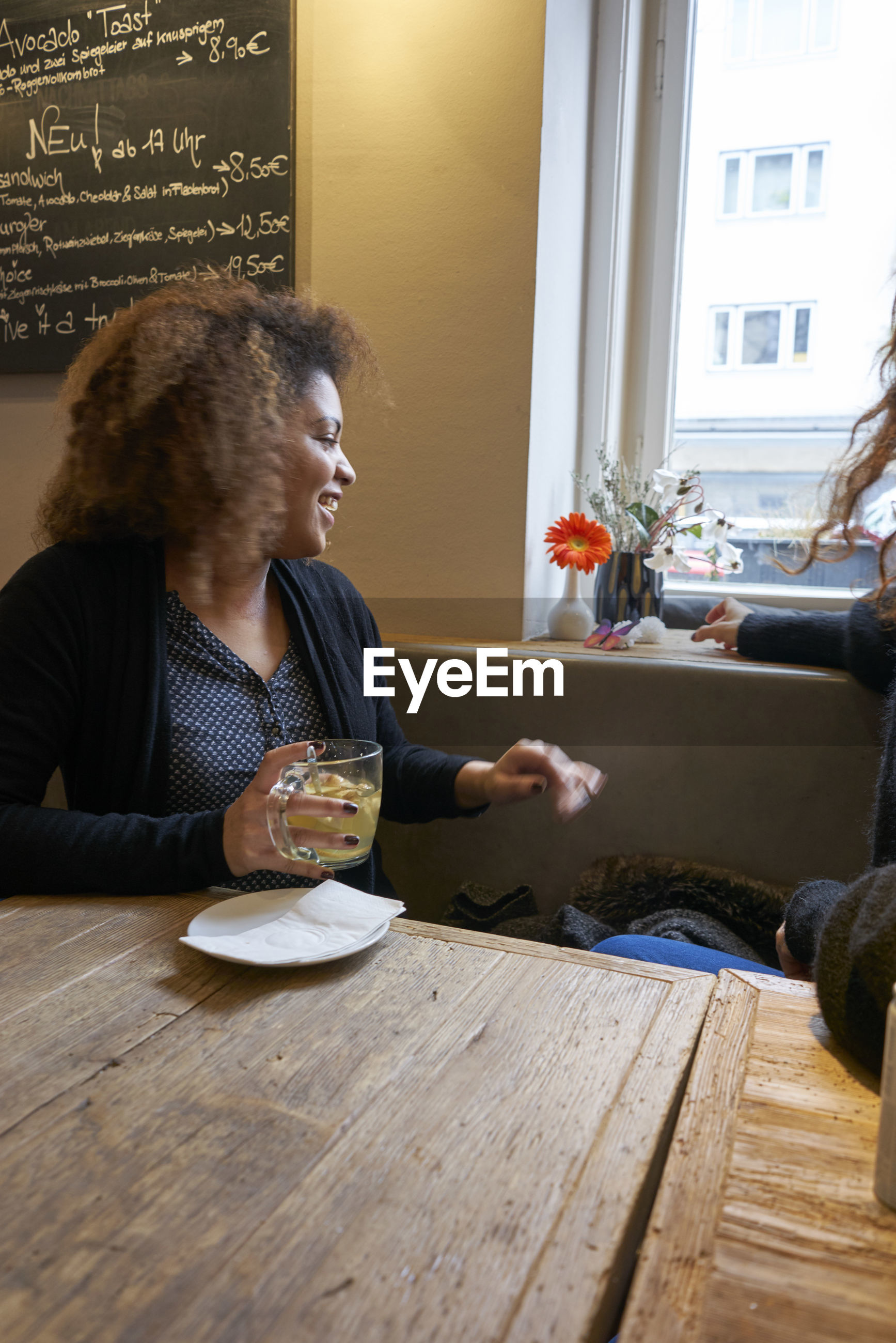 Smiling woman having tea while sitting with friend at restaurant