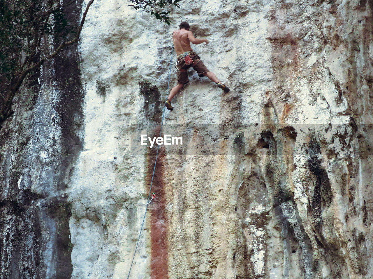 Rear View Of Shirtless Man Climbing Mountain
