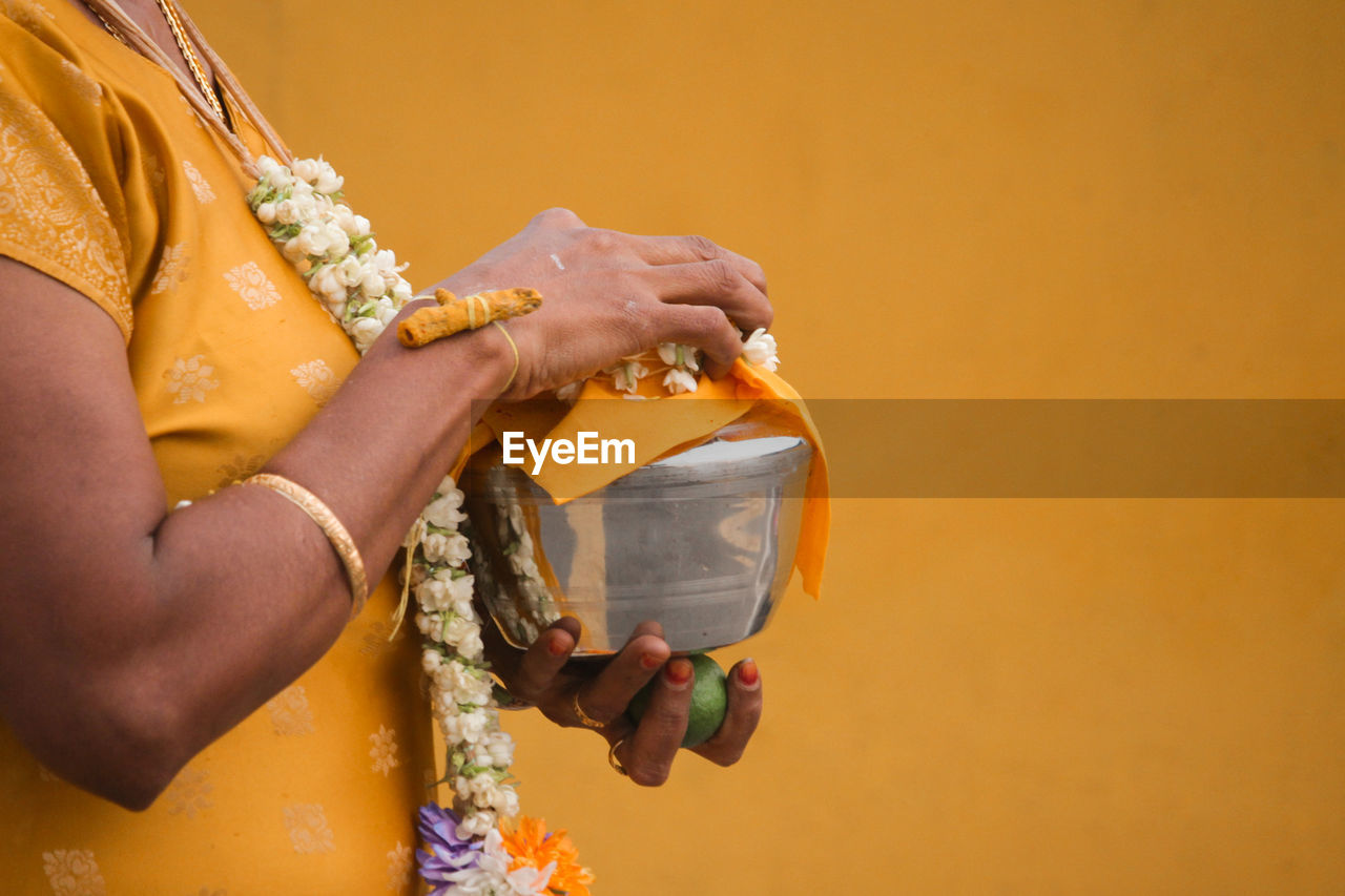 Midsection Of Woman Holding Religious Utensil Against Yellow