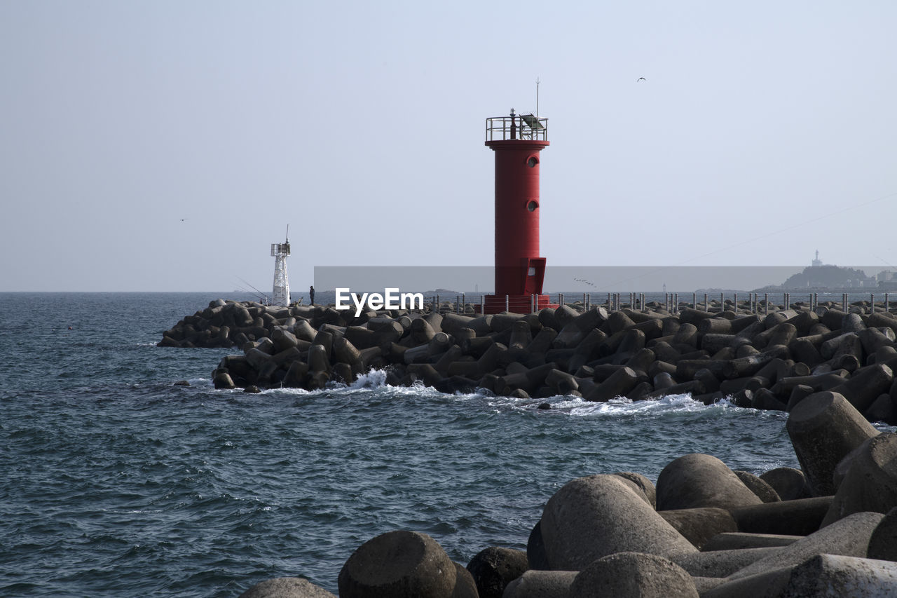 water, rock, sea, guidance, security, solid, rock - object, sky, lighthouse, tower, safety, protection, direction, built structure, nature, architecture, clear sky, scenics - nature, day, horizon over water, no people, outdoors, groyne