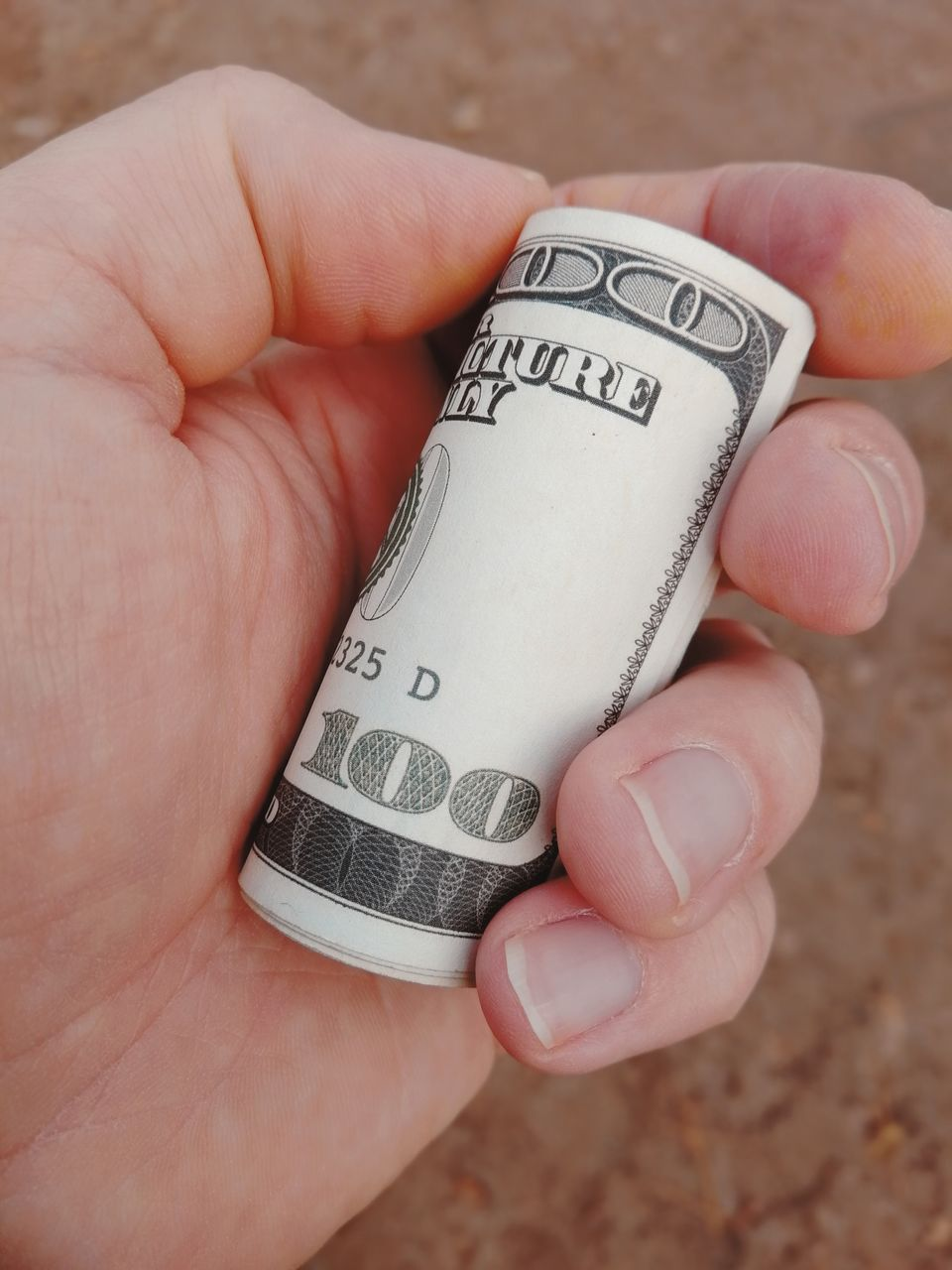 Close-Up Of Human Hand Holding Rolled Paper Currency Outdoors