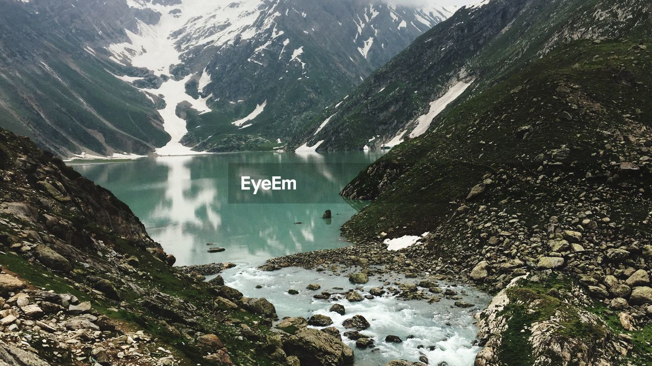 mountain, water, beauty in nature, rock, nature, snow, environment, travel, mountain range, cold temperature, landscape, winter, scenery, lake, outdoors, wilderness, rock - object, day, mountain peak, flowing water