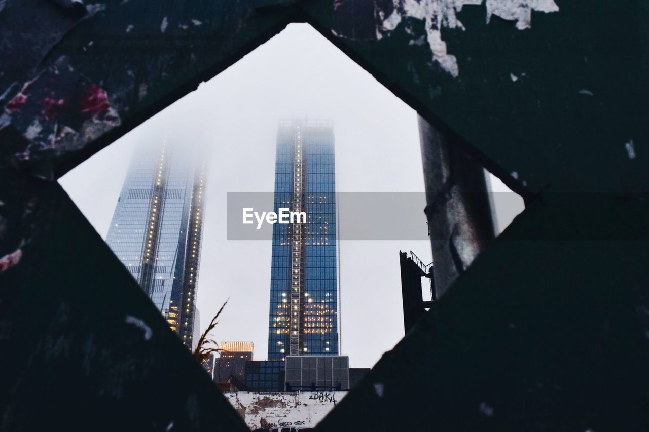 architecture, built structure, building, city, building exterior, skyscraper, office building exterior, sky, tall - high, nature, no people, travel destinations, silhouette, outdoors, tower, modern, day, low angle view, focus on background, cityscape, financial district