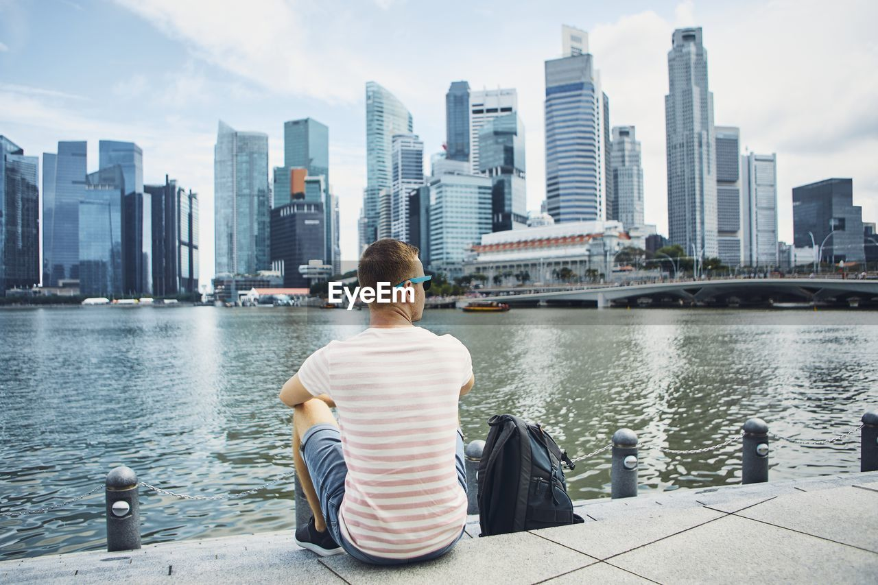 Rear View Of Man Sitting By River Against Buildings In City