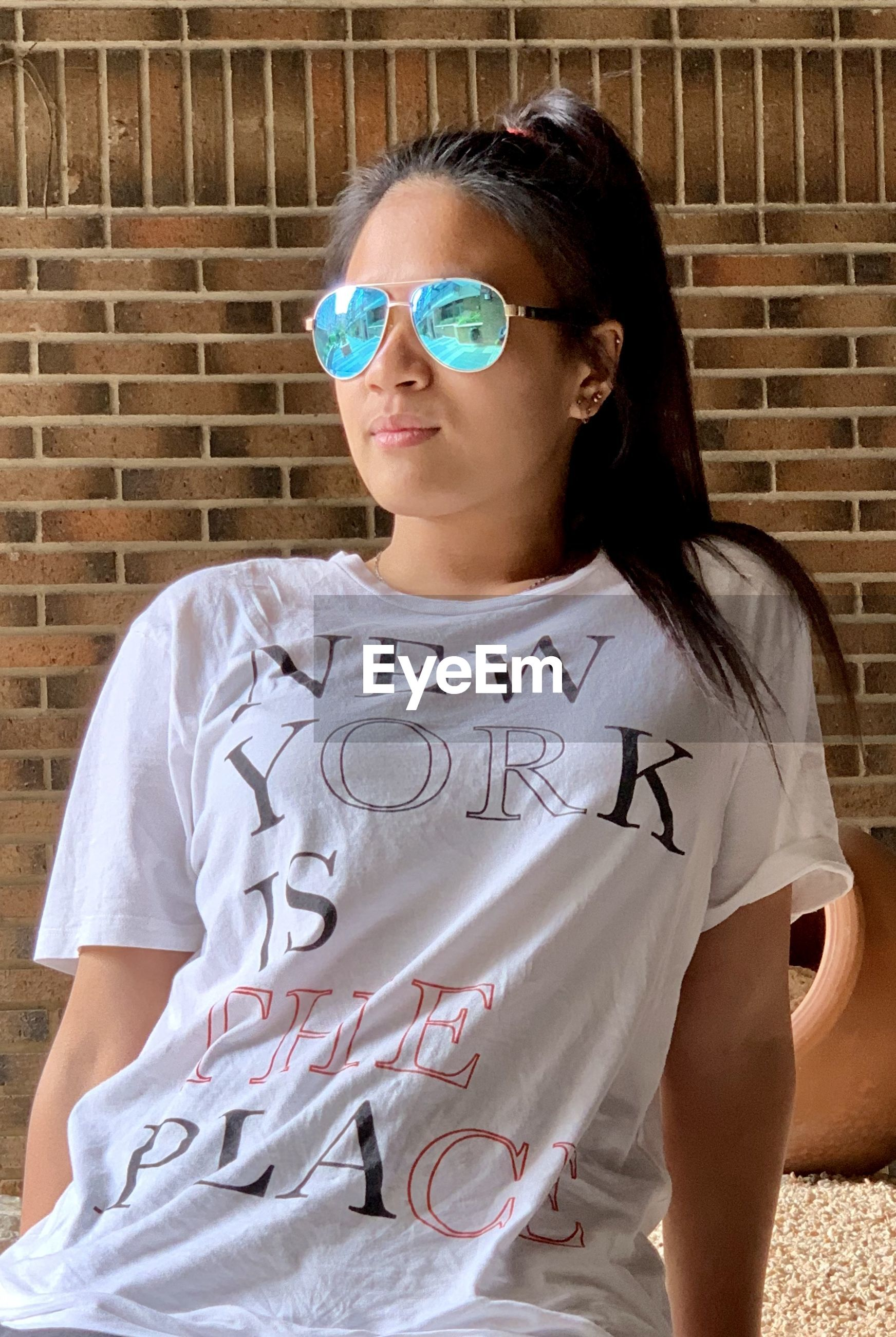 Woman wearing sunglasses while standing against wall