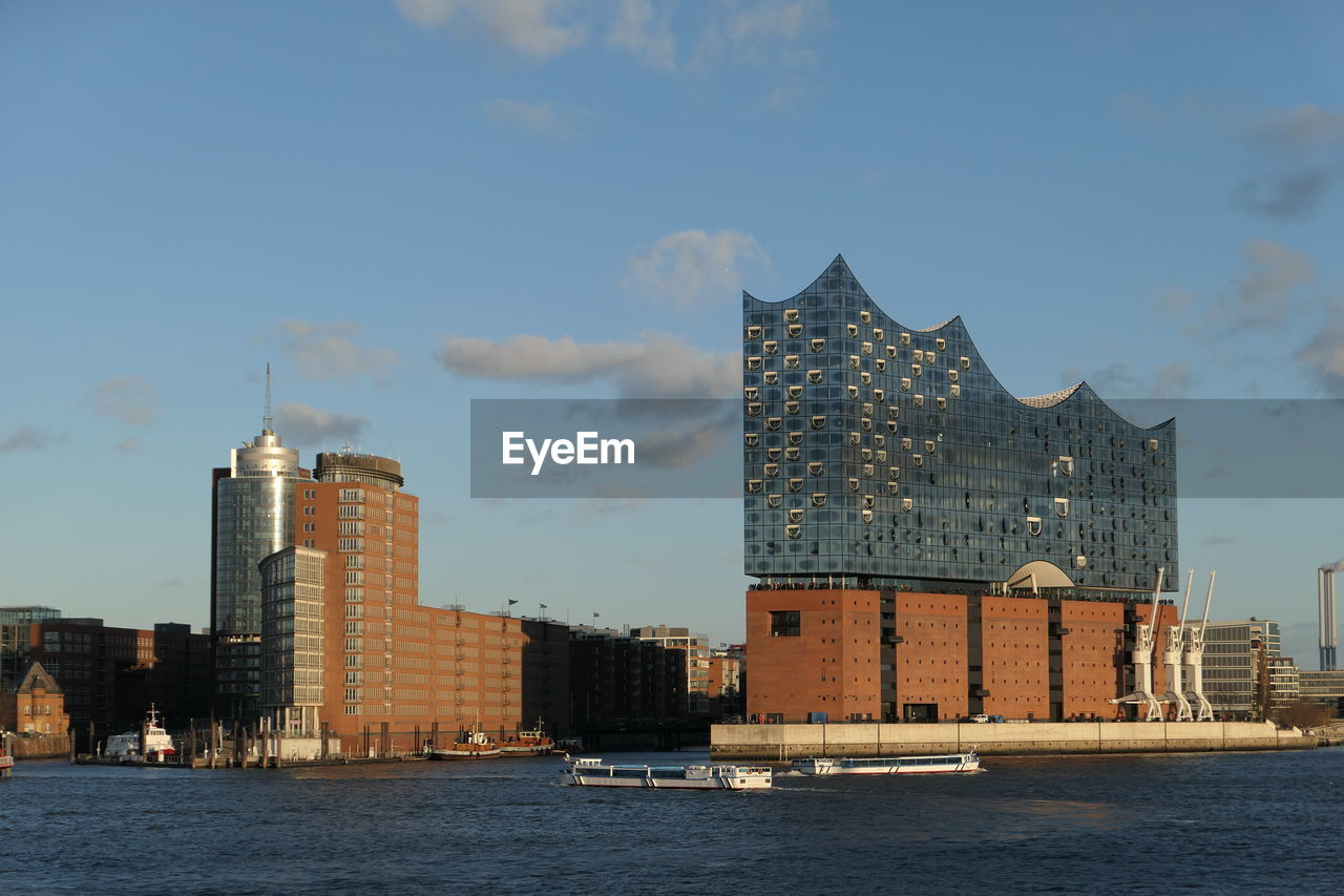architecture, sky, water, building exterior, building, built structure, waterfront, nautical vessel, city, transportation, nature, cloud - sky, modern, office building exterior, mode of transportation, no people, travel, outdoors, sea, skyscraper, financial district