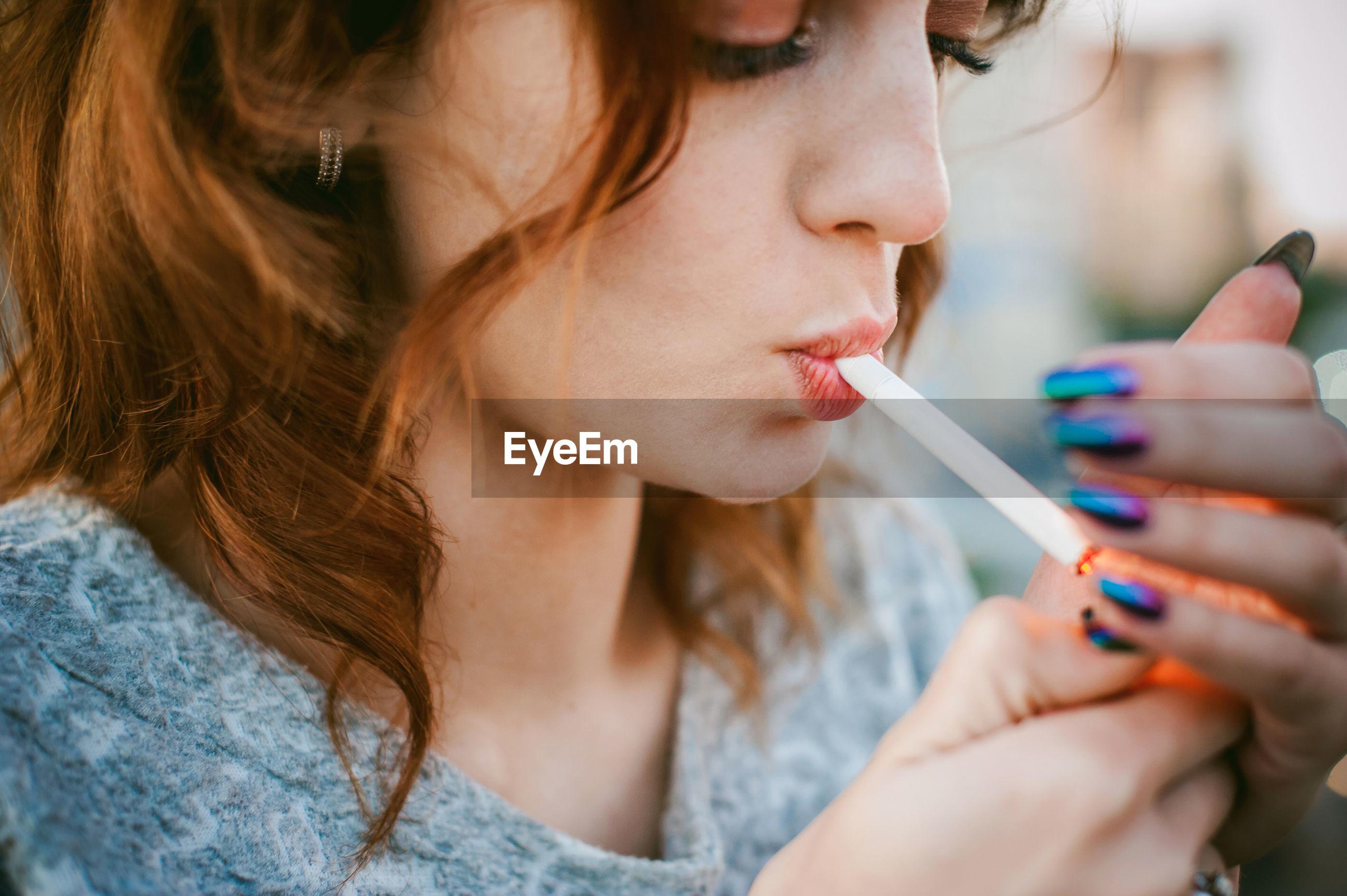 Close-up of beautiful woman smoking cigarette
