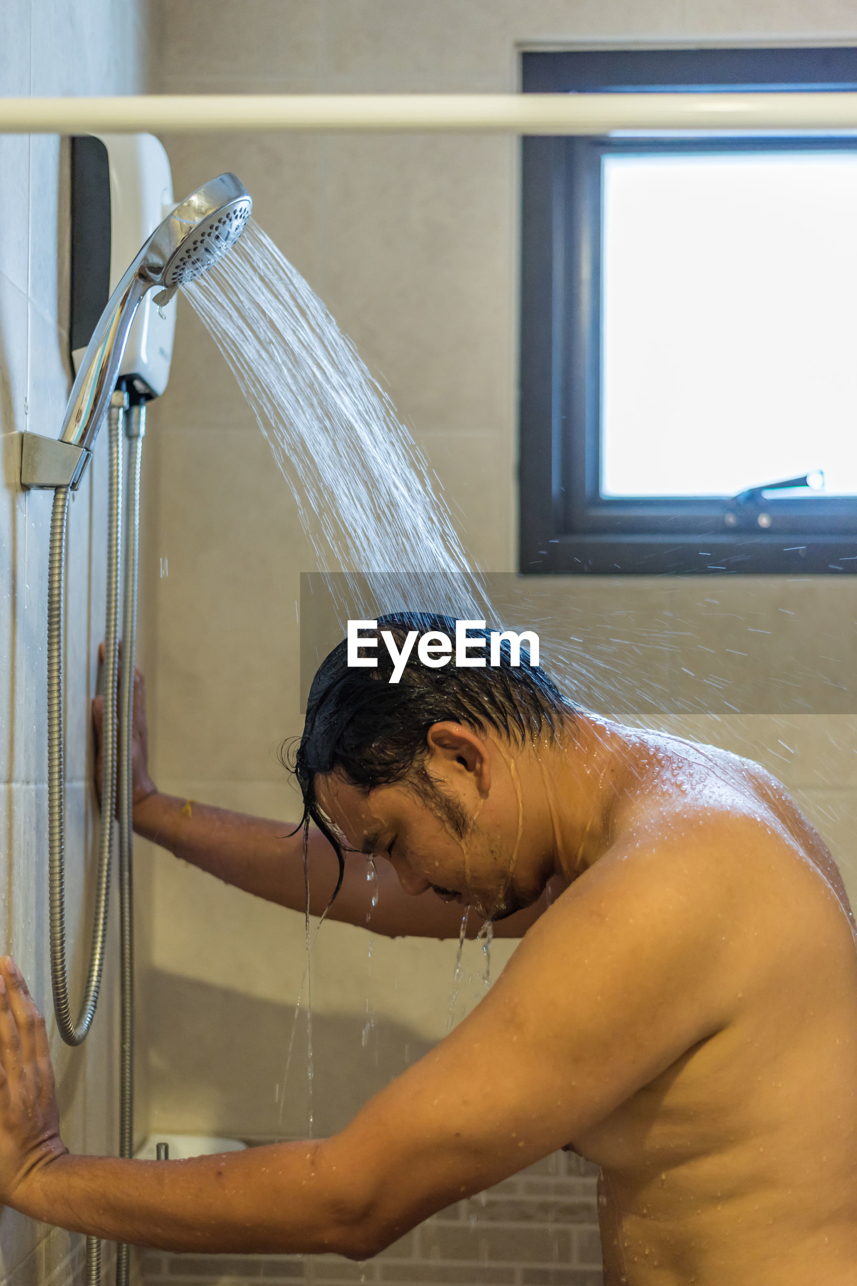 Side view of man taking shower in bathroom