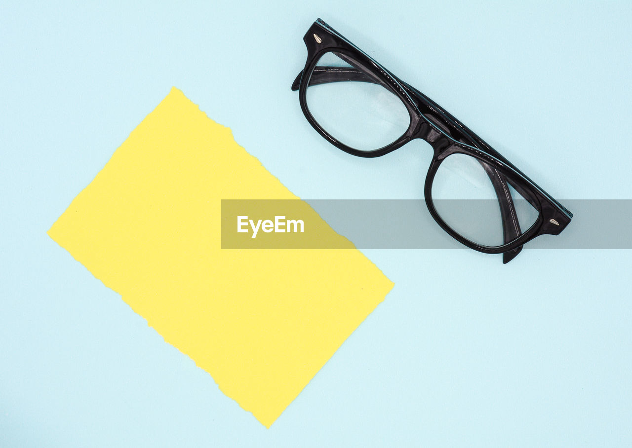studio shot, yellow, glasses, eyeglasses, indoors, white background, no people, cut out, still life, paper, copy space, close-up, blue, personal accessory, adhesive note, note, blank, single object, simplicity, black color, eyewear, blue background