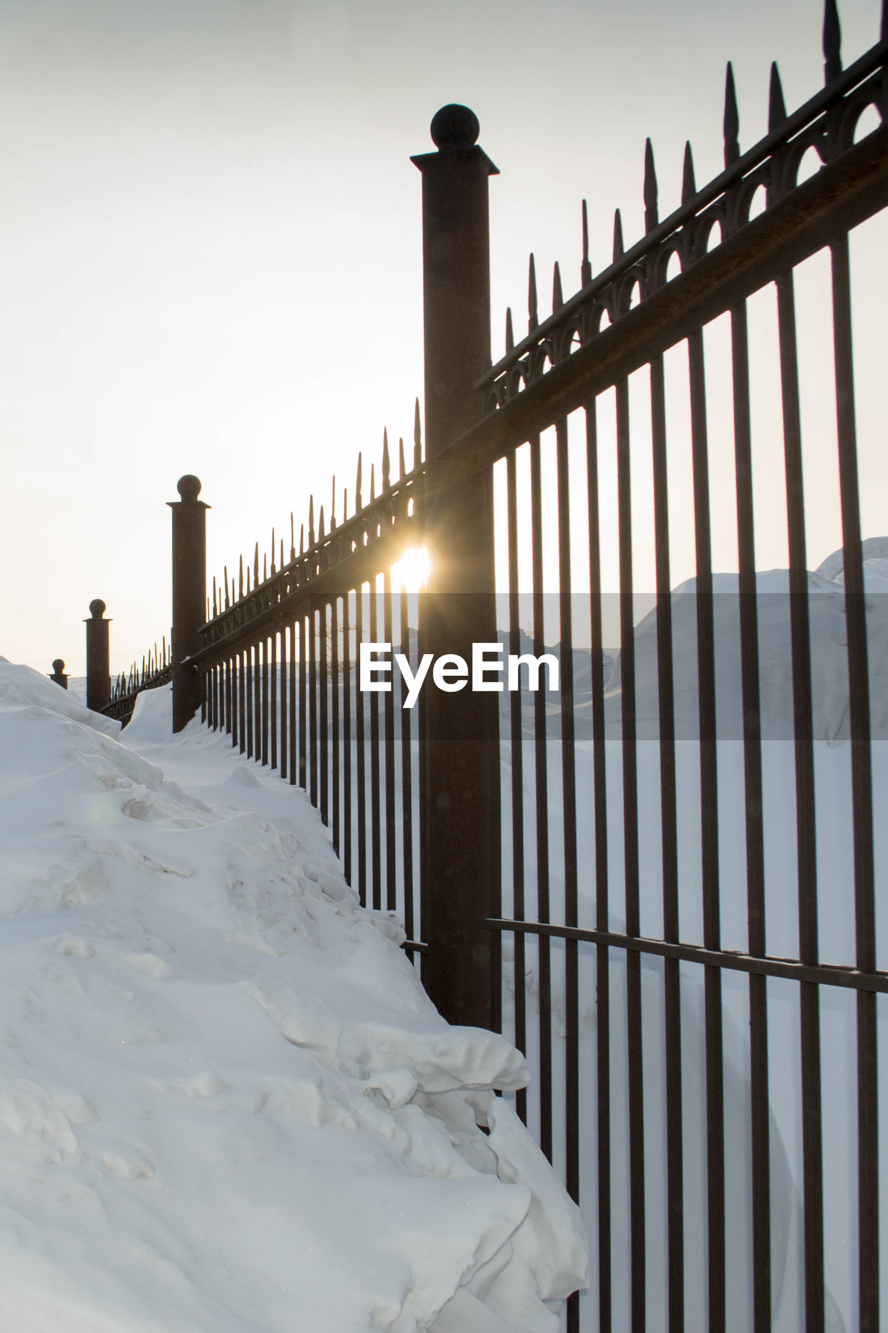 SNOW COVERED RAILING AGAINST FENCE DURING WINTER