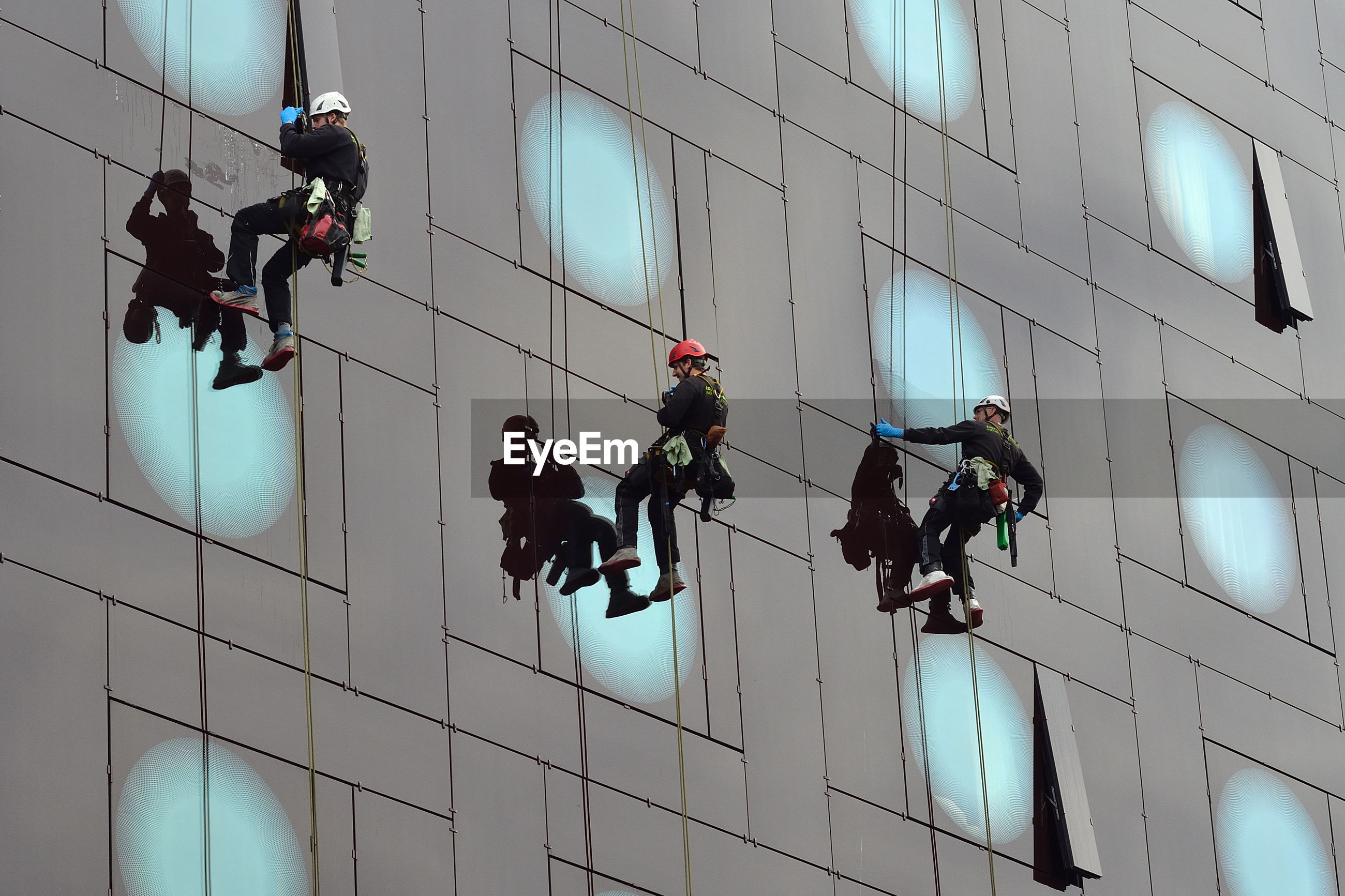 LOW ANGLE VIEW OF PEOPLE WORKING ON ROPE TIED TO BUILDING