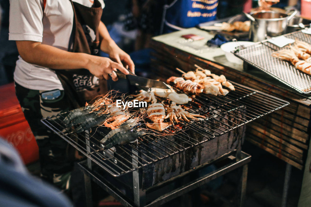 Midsection of woman preparing food on barbecue grill