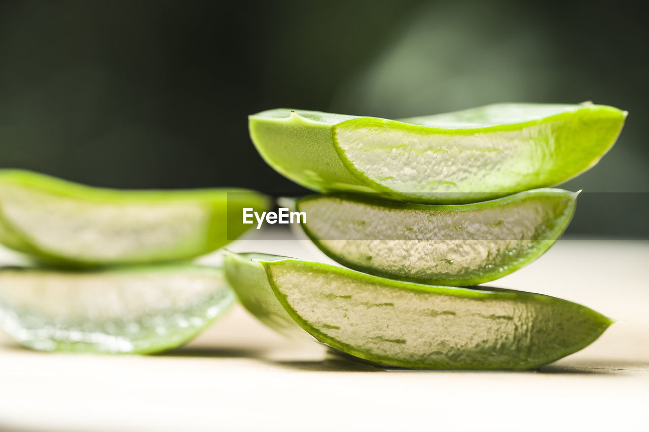 green color, close-up, freshness, indoors, still life, wellbeing, leaf, slice, no people, plant part, selective focus, food, food and drink, healthy eating, fruit, plant, focus on foreground, studio shot, nature, vegetable, leaves, pebble