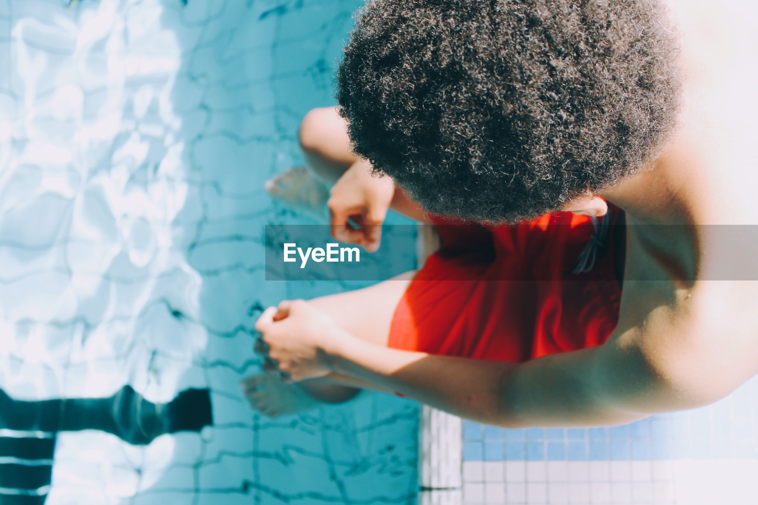 High angle view of boy sitting by poolside
