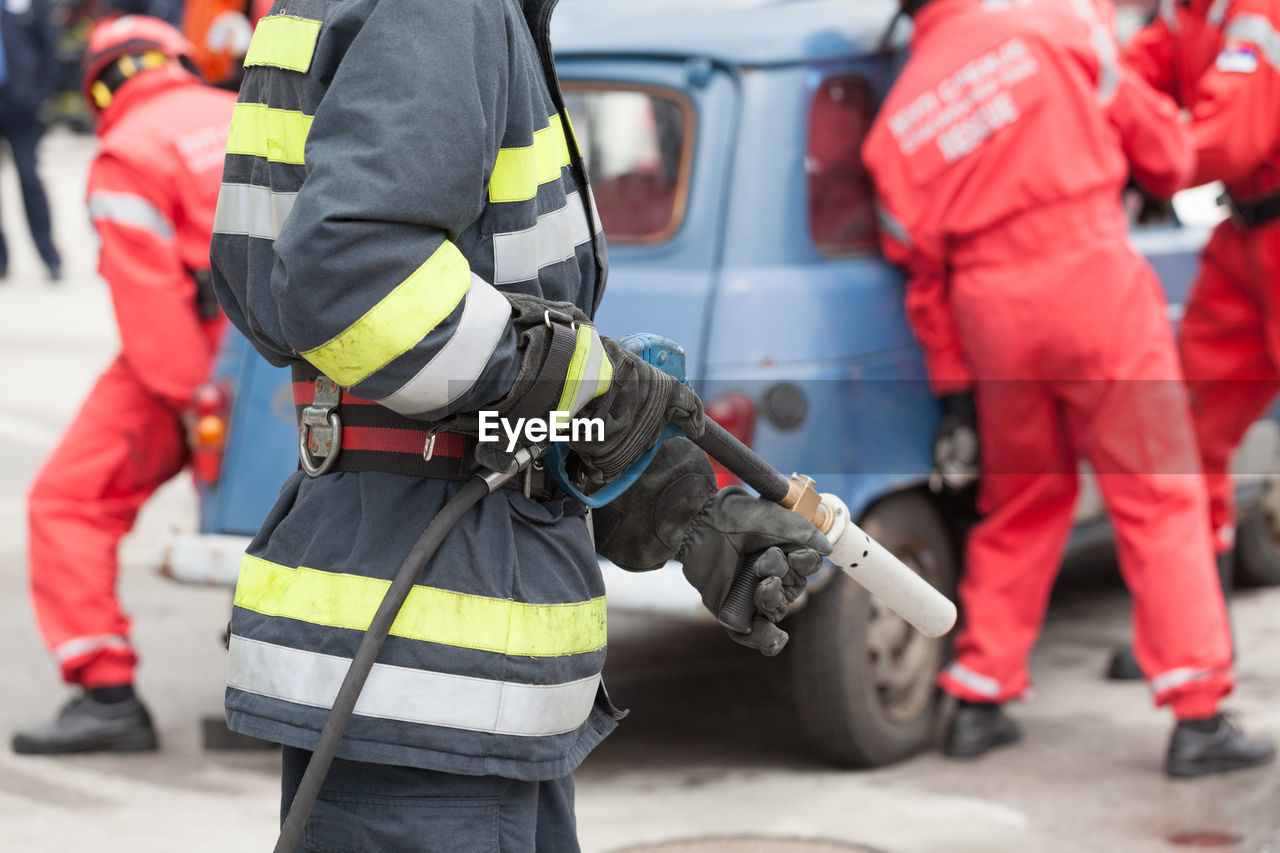 Midsection Of Firefighter Standing On Road