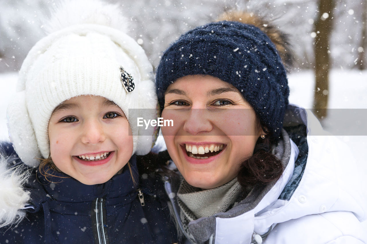 PORTRAIT OF SMILING BOY IN SNOW DURING WINTER