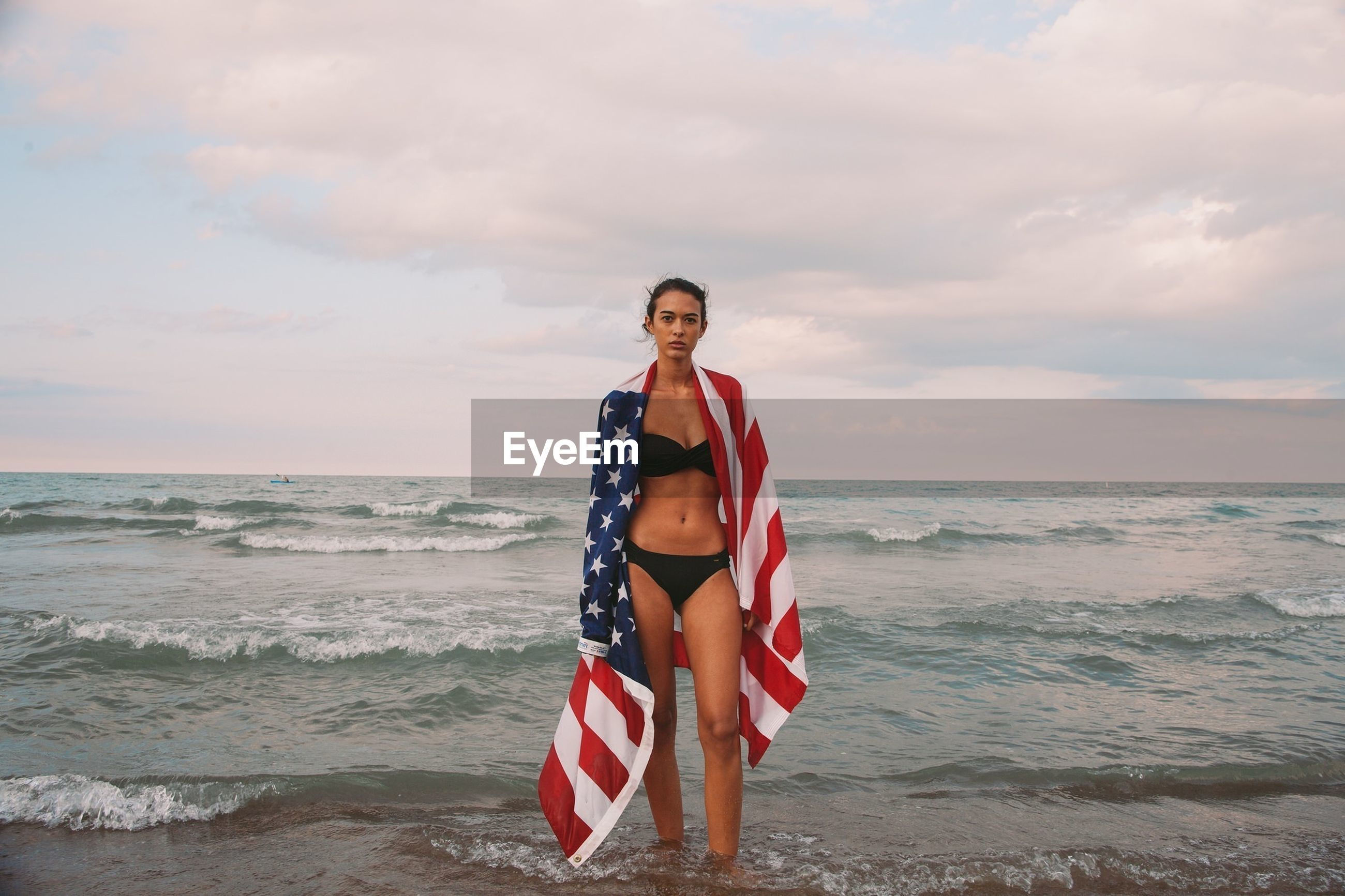 PORTRAIT OF BEAUTIFUL WOMAN STANDING AT BEACH AGAINST SKY