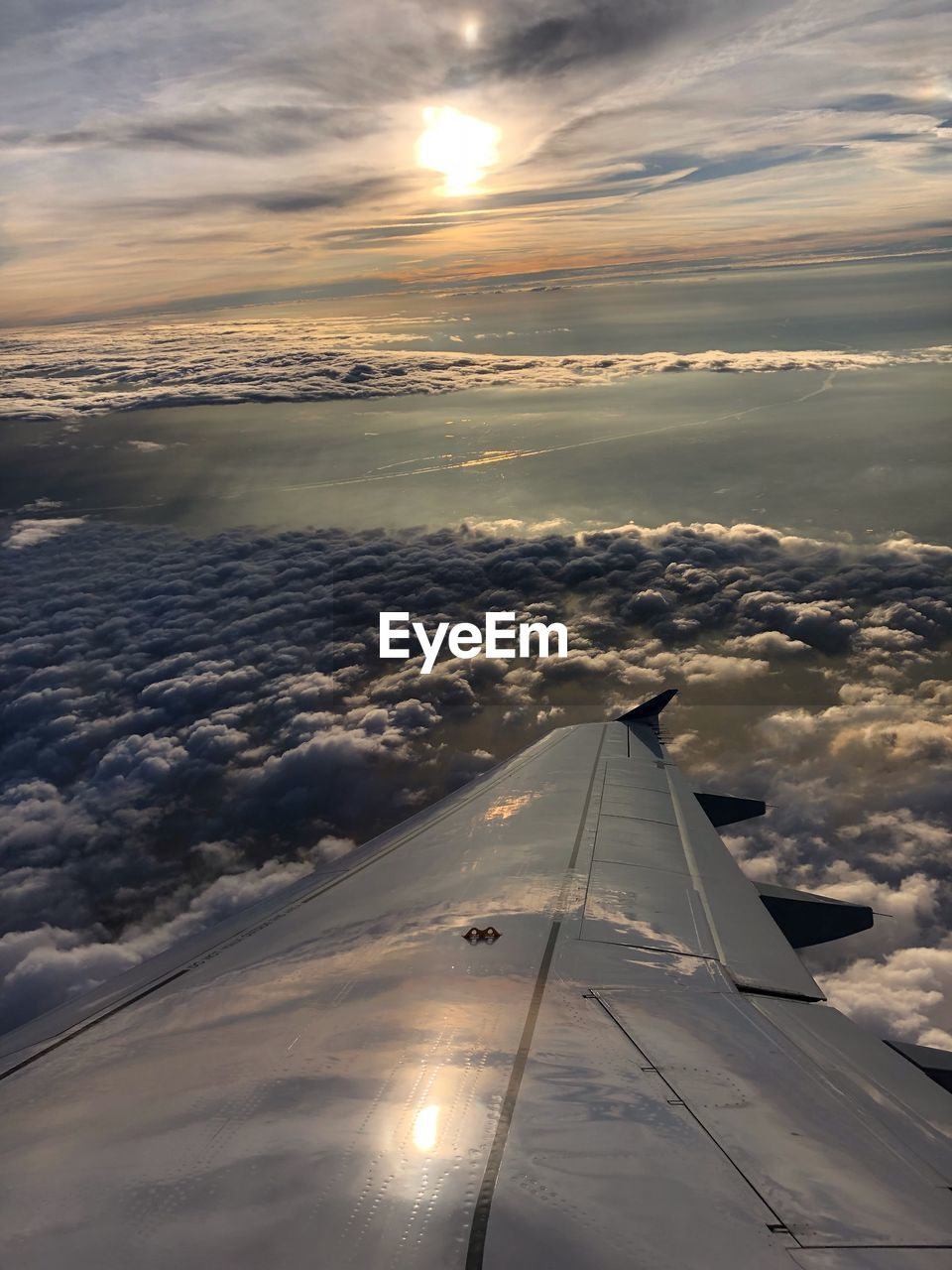 cloud - sky, sky, air vehicle, airplane, transportation, mode of transportation, aircraft wing, flying, sunset, beauty in nature, scenics - nature, no people, nature, mid-air, sun, aerial view, travel, sunlight, outdoors, on the move, above, plane