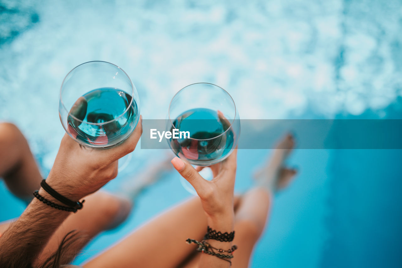 CLOSE-UP OF HANDS HOLDING SWIMMING POOL