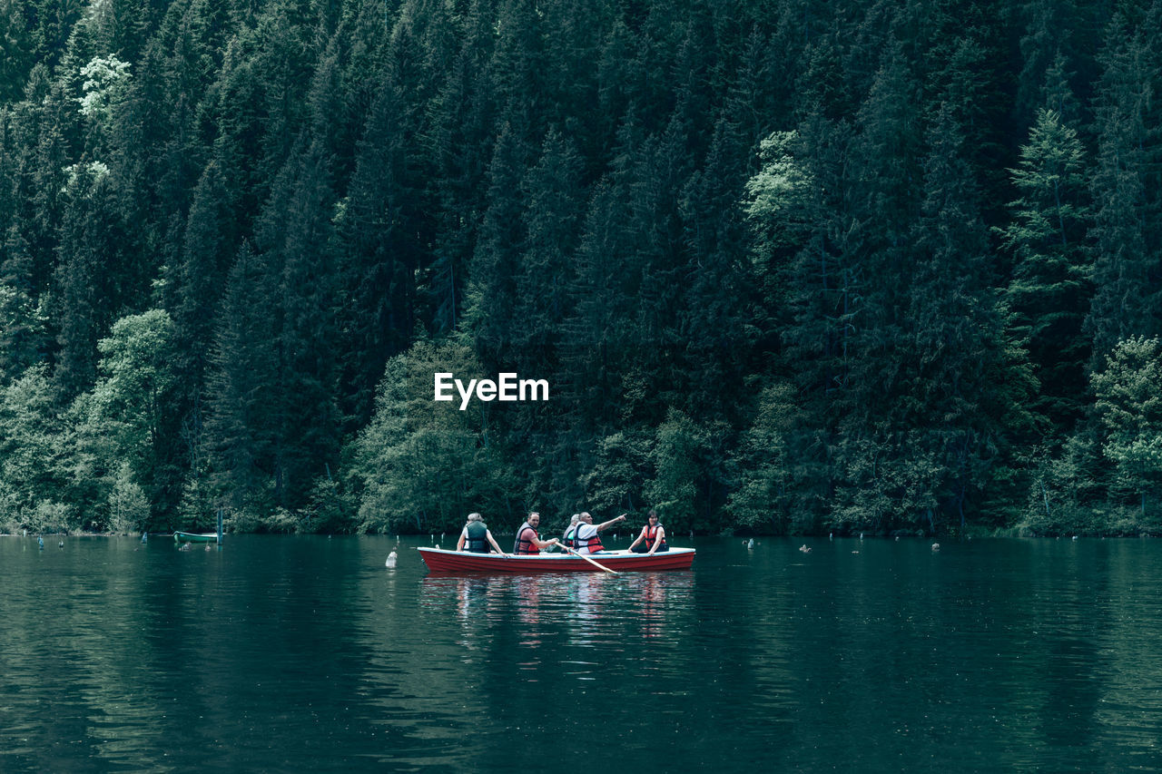 People On Boat In Lake Against Trees In Forest