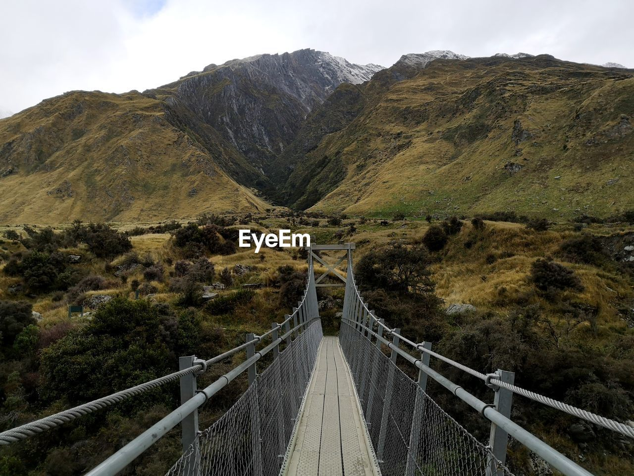 Footbridge over mountain against sky