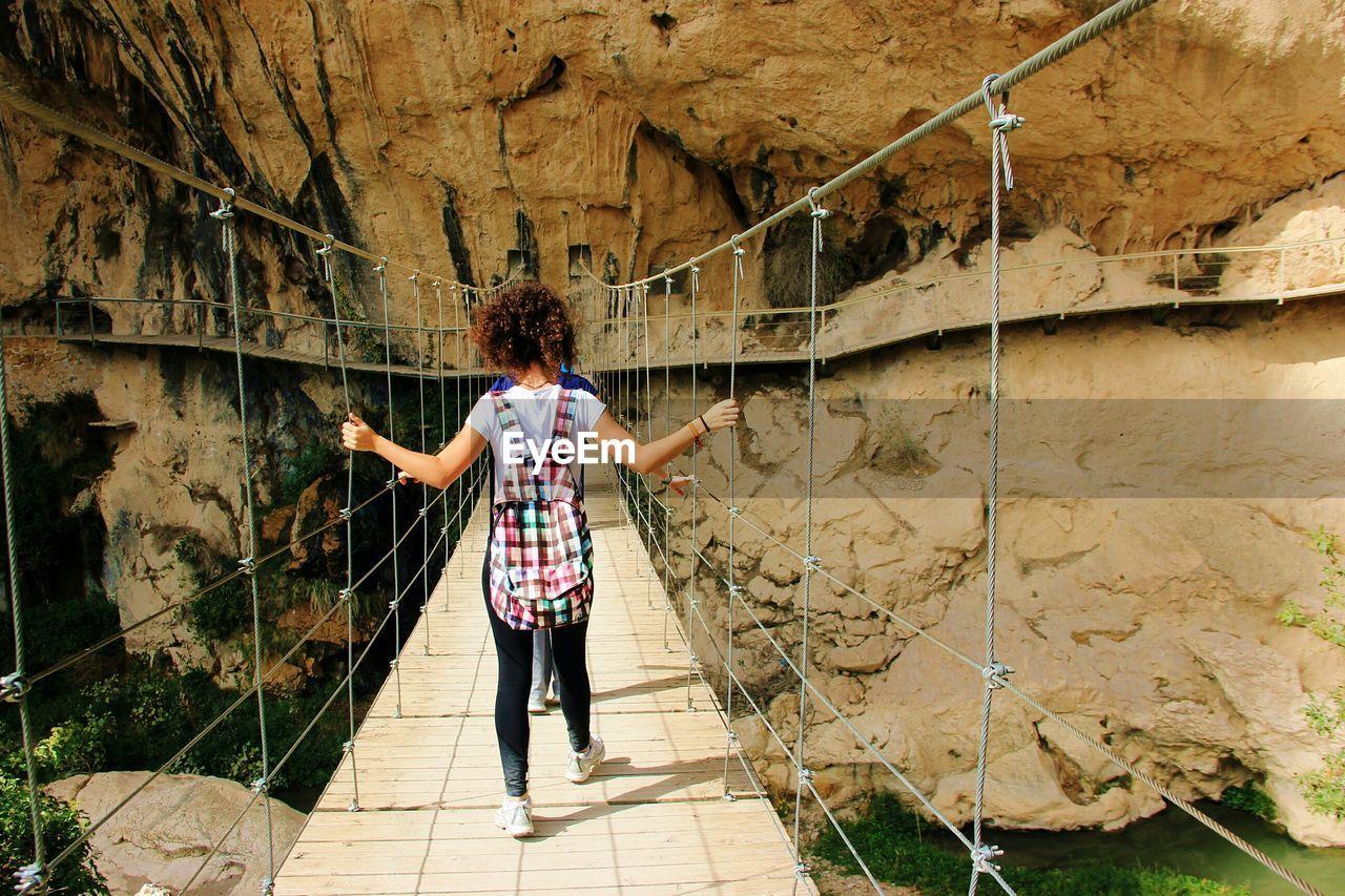 Rear view of woman walking on footbridge leading towards rock formations