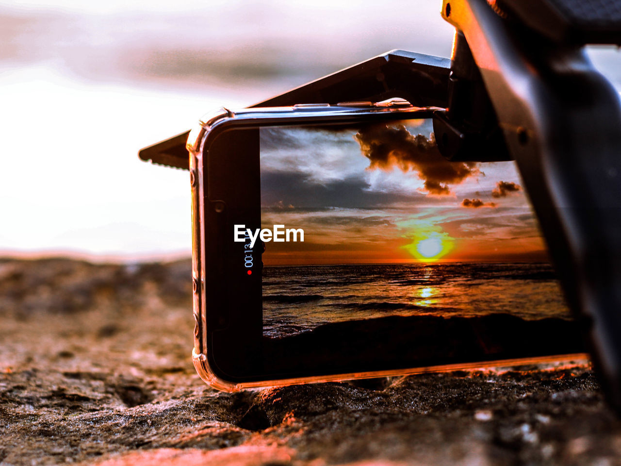sky, sunset, nature, technology, cloud - sky, communication, smart phone, land, close-up, selective focus, outdoors, water, wireless technology, mobile phone, screen, portable information device, scenics - nature, photography themes, focus on foreground, no people