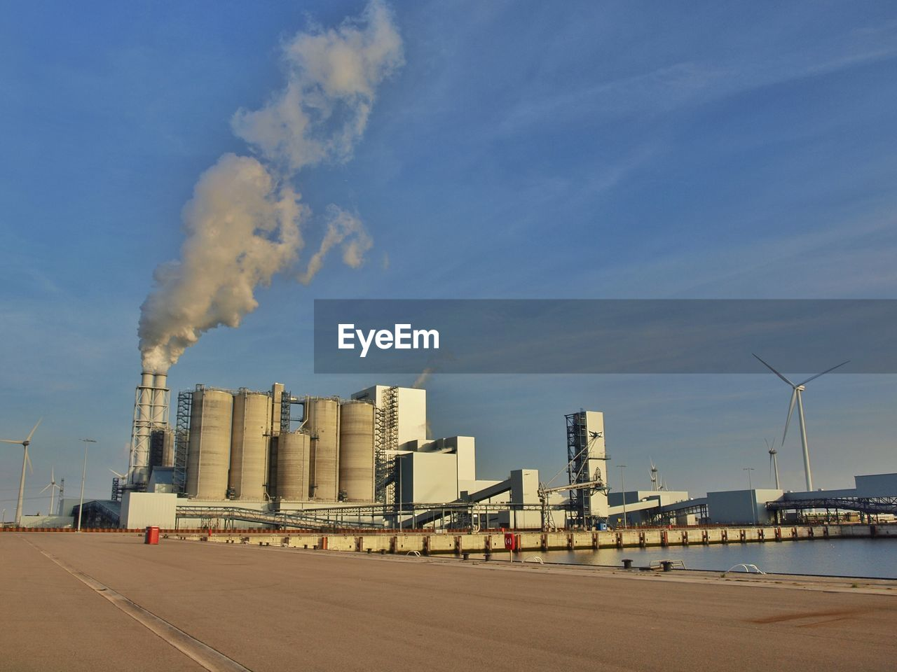 Factory Emitting Pollution Against Blue Sky