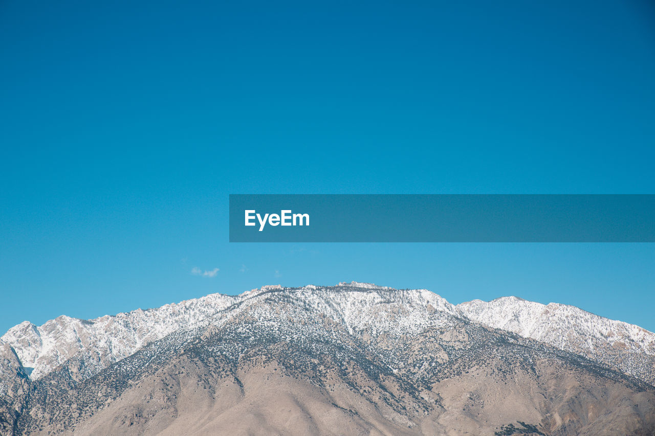 LOW ANGLE VIEW OF SNOW COVERED MOUNTAIN AGAINST CLEAR BLUE SKY