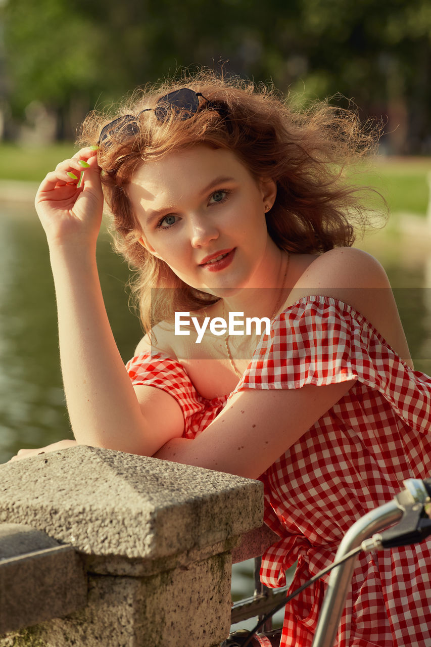 Beautiful girl with red dress and curly red hair looking at camera in sun light