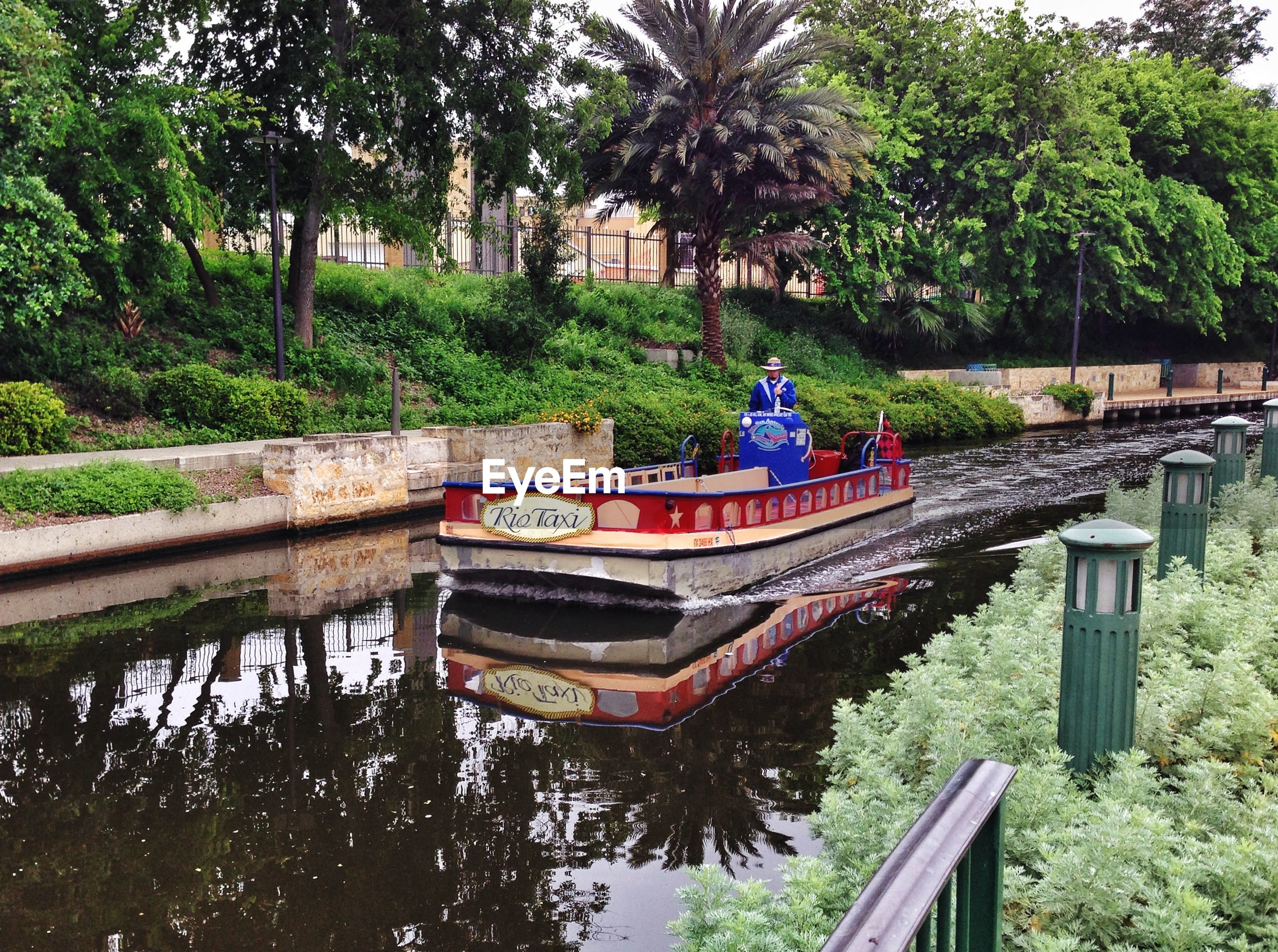 Boat on canal against trees